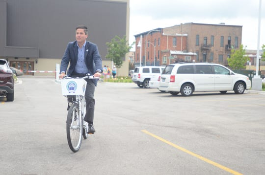 Port Huron City Manager James Freed takes the first official ride of a rental bicycle in July 2017 around the parking lot of Blue Water Transit's bus hub.