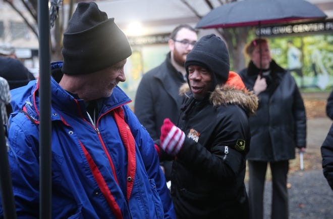 Calvin Ware, right, a homeless man who resides in Kingston, greets Duane Byble, left, a formerly homeless city of Poughkeepsie resident, at a vigil in the city marking Homeless Persons' Remembrance Day. They both said being homeless becomes more challenging when it gets colder outside.