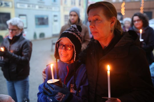 Jane Gray, right, a Hudson River Housing employee, holds a candle and wraps her arm around Kelly Cash, who lives in a shelter run by the agency. They were marking Homeless Persons' Remembrance Day in the city of Poughkeepsie.