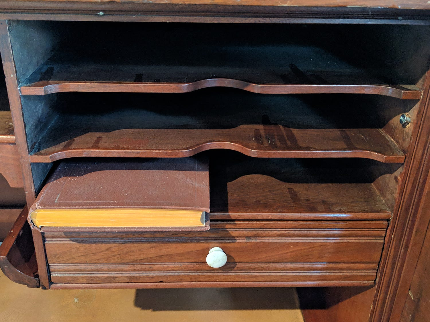 Dividers and drawers inside the desk can be hidden with the roll-top.