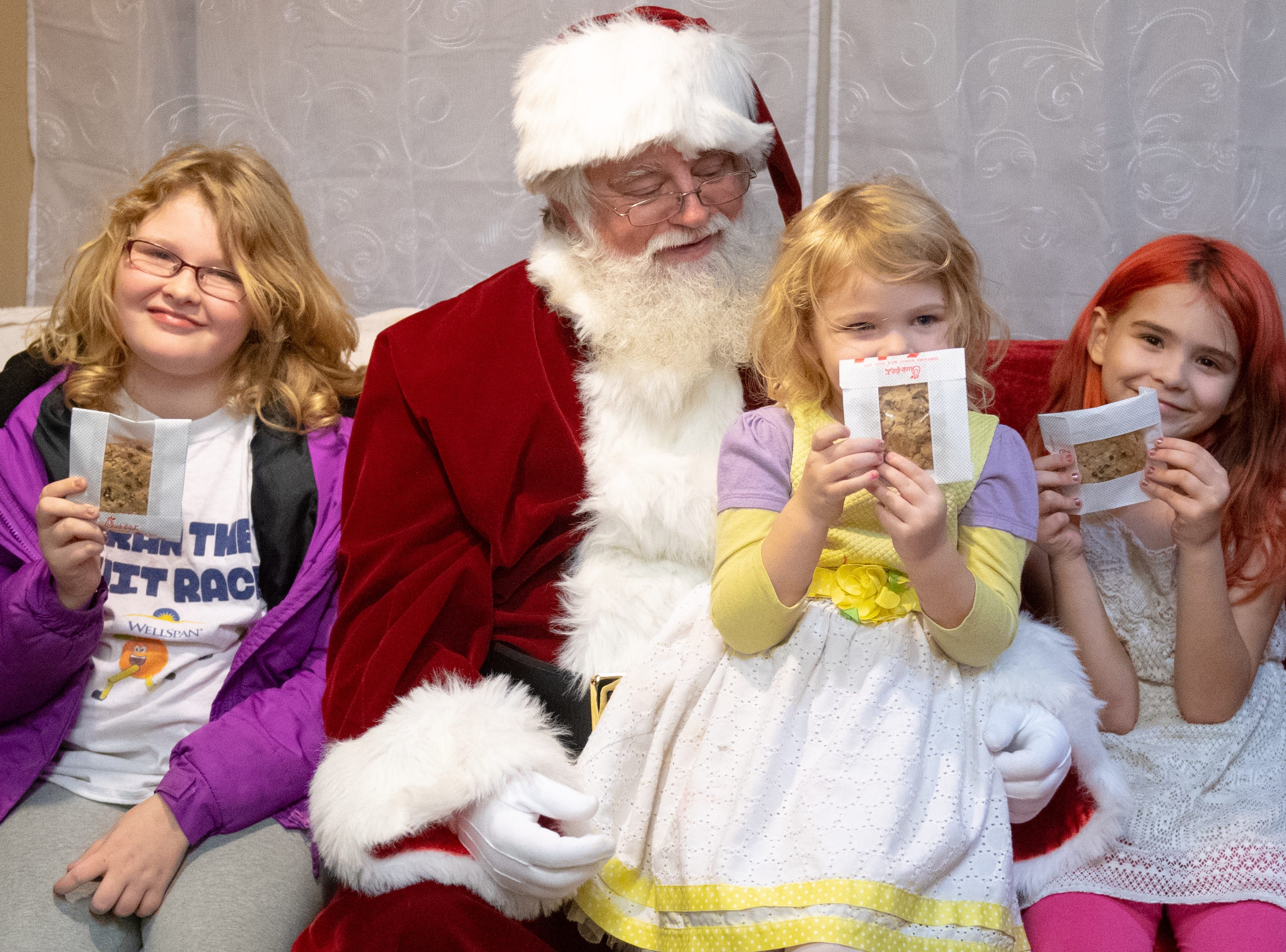 Sisters (left to right) Elizabeth, 9, Kimberly, 4, and Bethine Henwood, 7, show off their sweet treats during the Dinner with Santa and Santa Cow event, December 19, 2018.