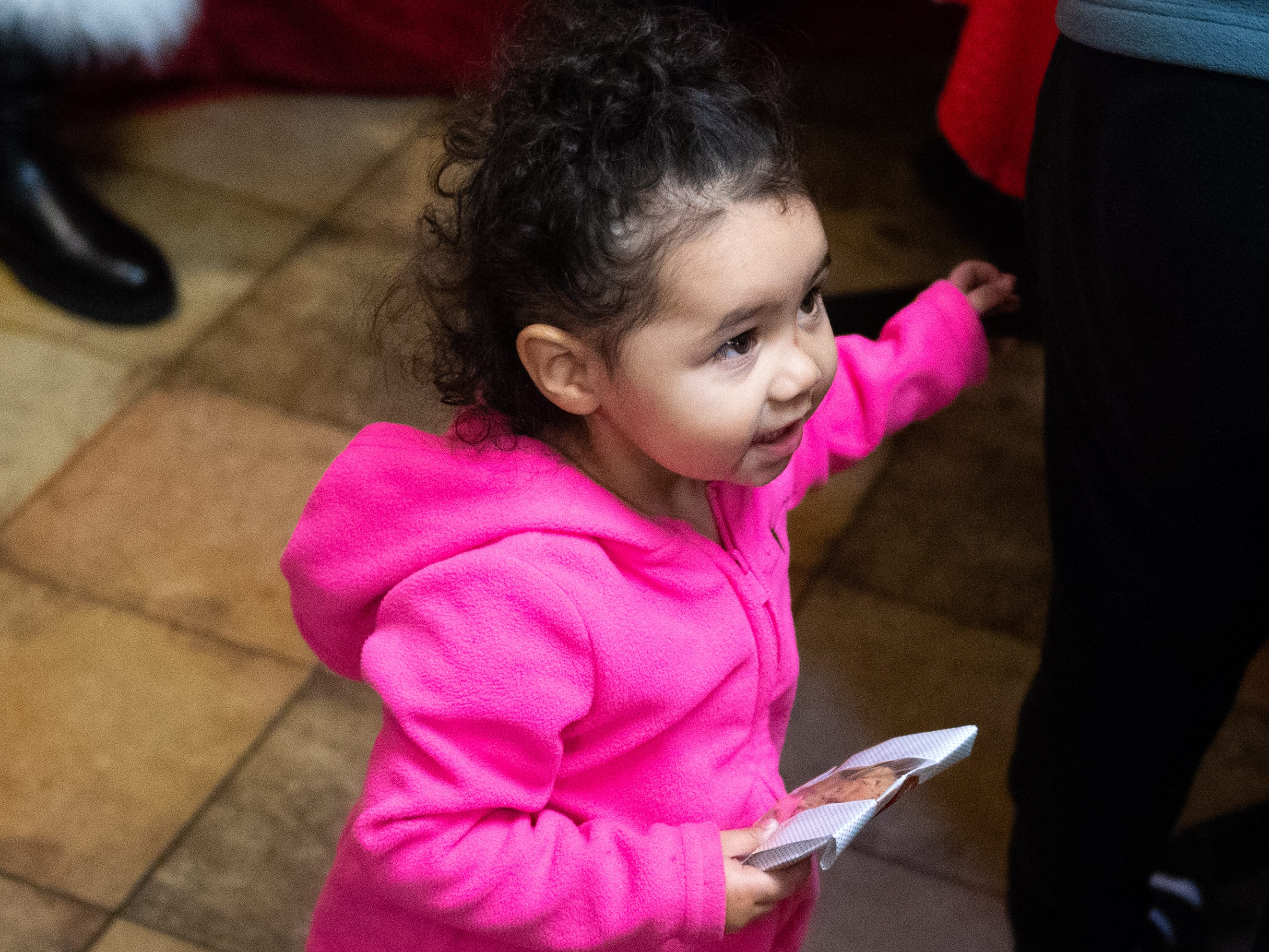 Children like Isabella Maldonado, 1, receive a cookie after sitting on Santa's lap during the Dinner with Santa and Santa Cow event at Chick-fil-A in East York, December 19, 2018.