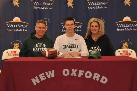 New Oxford's Connor Becker, center, has signed a national letter of intent to play football at Stetson University. He is flanked by Luke Becker, left, and Carrie Becker at the signing.
