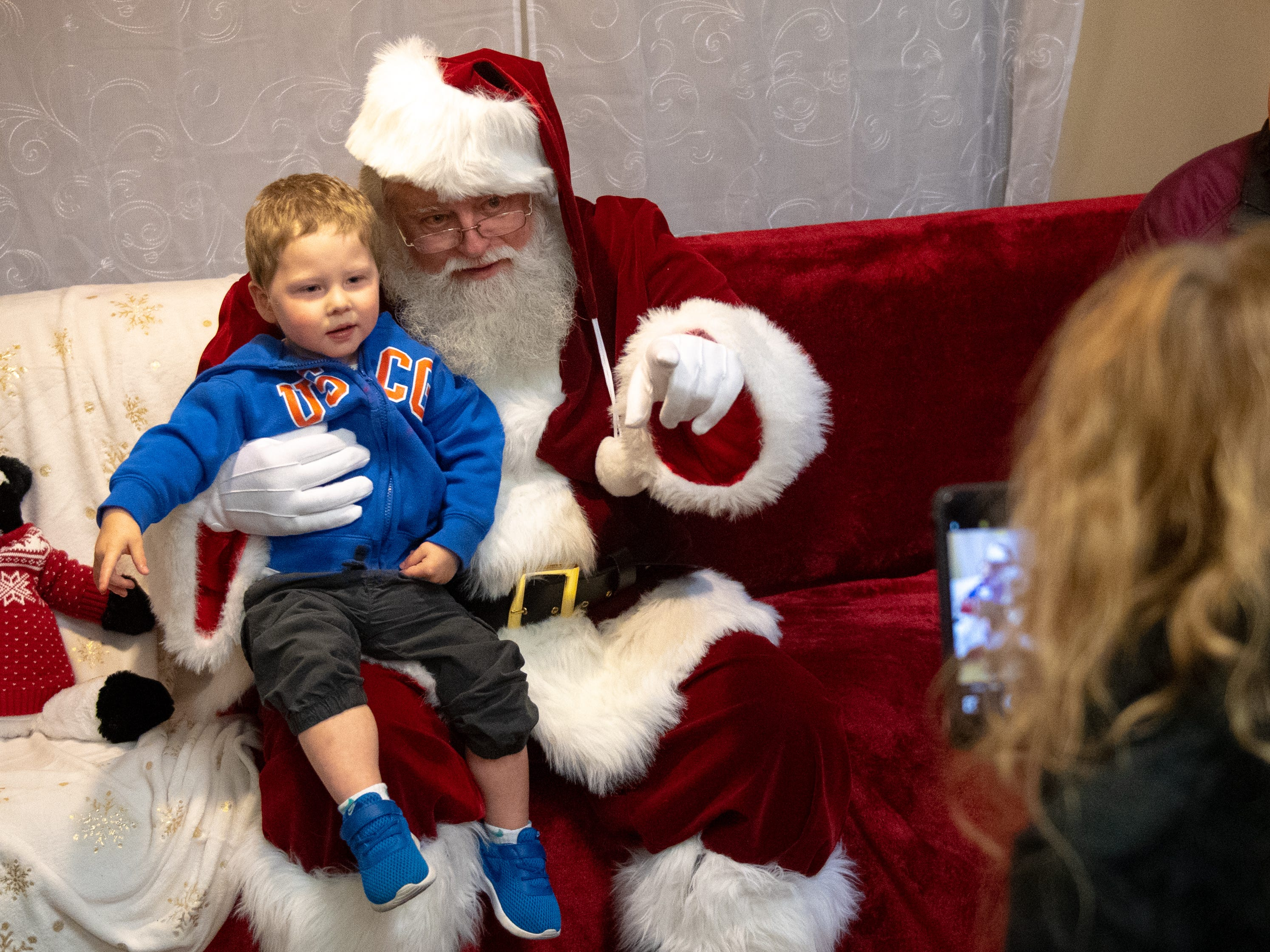 Carson Wertz, 2, of Newberry Township, poses with old Saint Nick for a photo during the Dinner with Santa and Santa Cow at Chick-fil-A in Springettsbury Township. Children were taught a few words in sign language as part of the special night designed to promote inclusion for the hearing-impaired community .