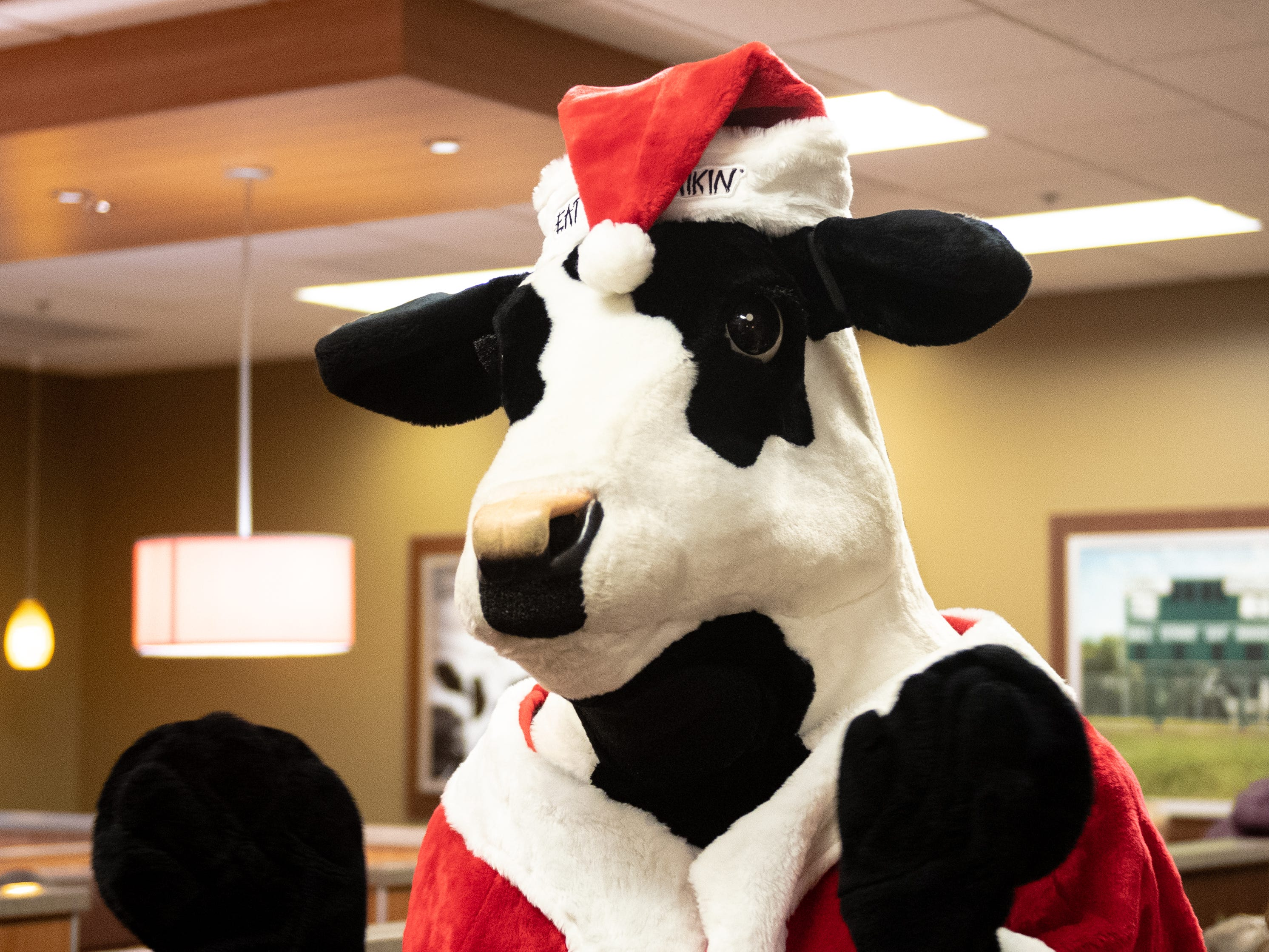 Santa Cow walks around the packed Chick-fil-A taking pictures with young guests and their parents during the Dinner with Santa and Santa Cow event Wednesday night.