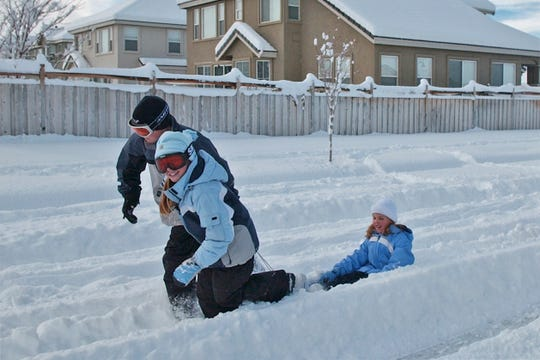 Haylee Ponte, 9, front, and D.J. Ponte, 12, pull Allyson Ghlert, 9, on a sled on Friday morning in Wingfield Springs.