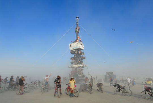 """Burners climb on an art installation titled """"Night of the Climb"""" by Dustin Weatherford at Burning Man on Aug. 27, 2018."""