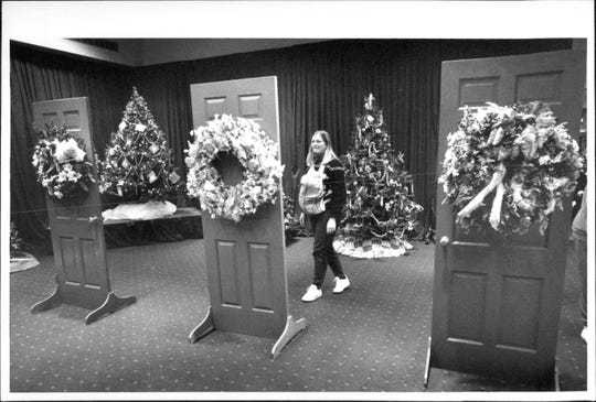Lauren Judson with baby Davis look at some of the wreaths decorating the door display in the Festival of Trees at the Convention Center in 1988.