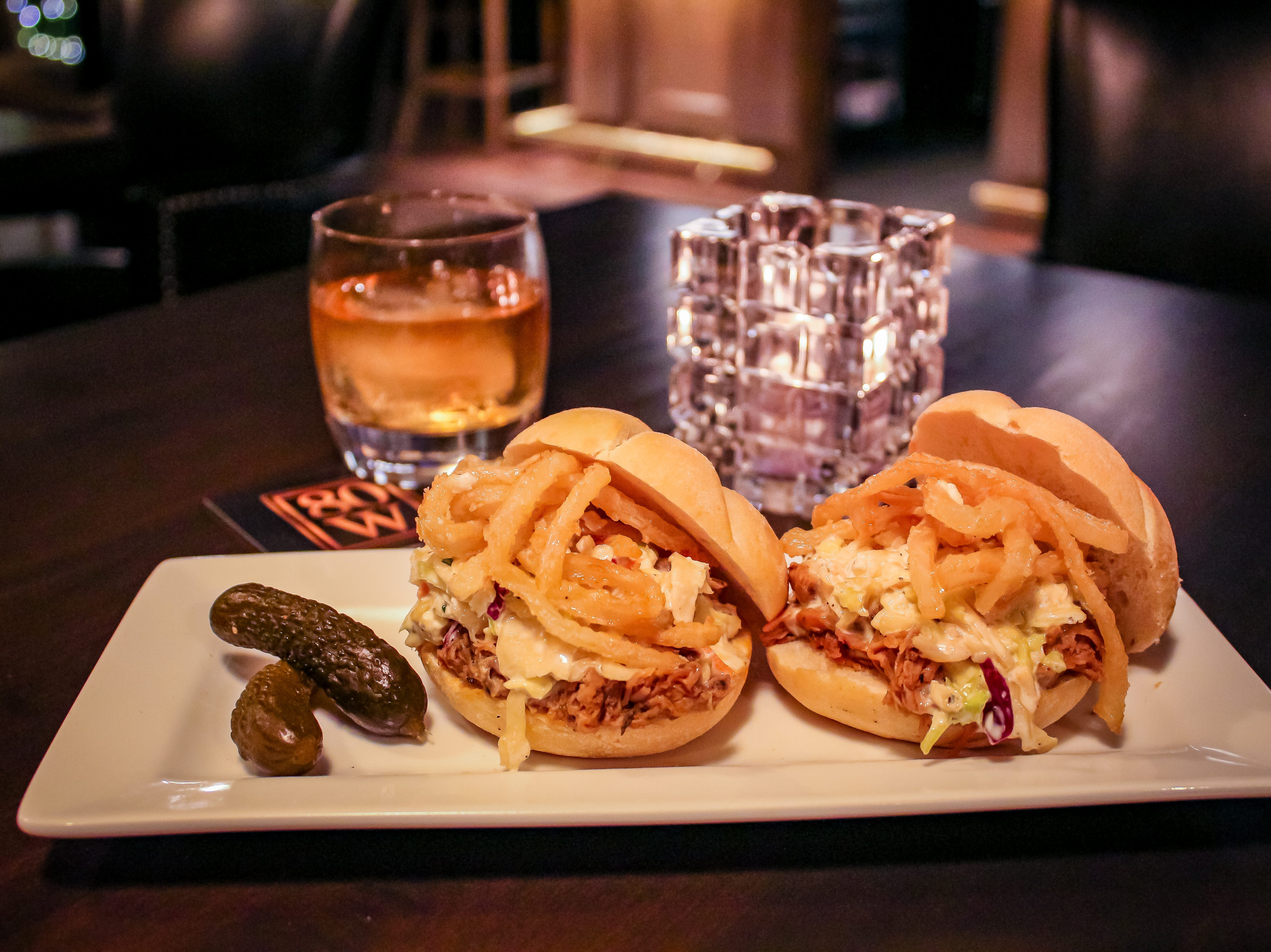 Pulled pork sliders are topped with blue cheese slaw, crispy onions and pickles.
