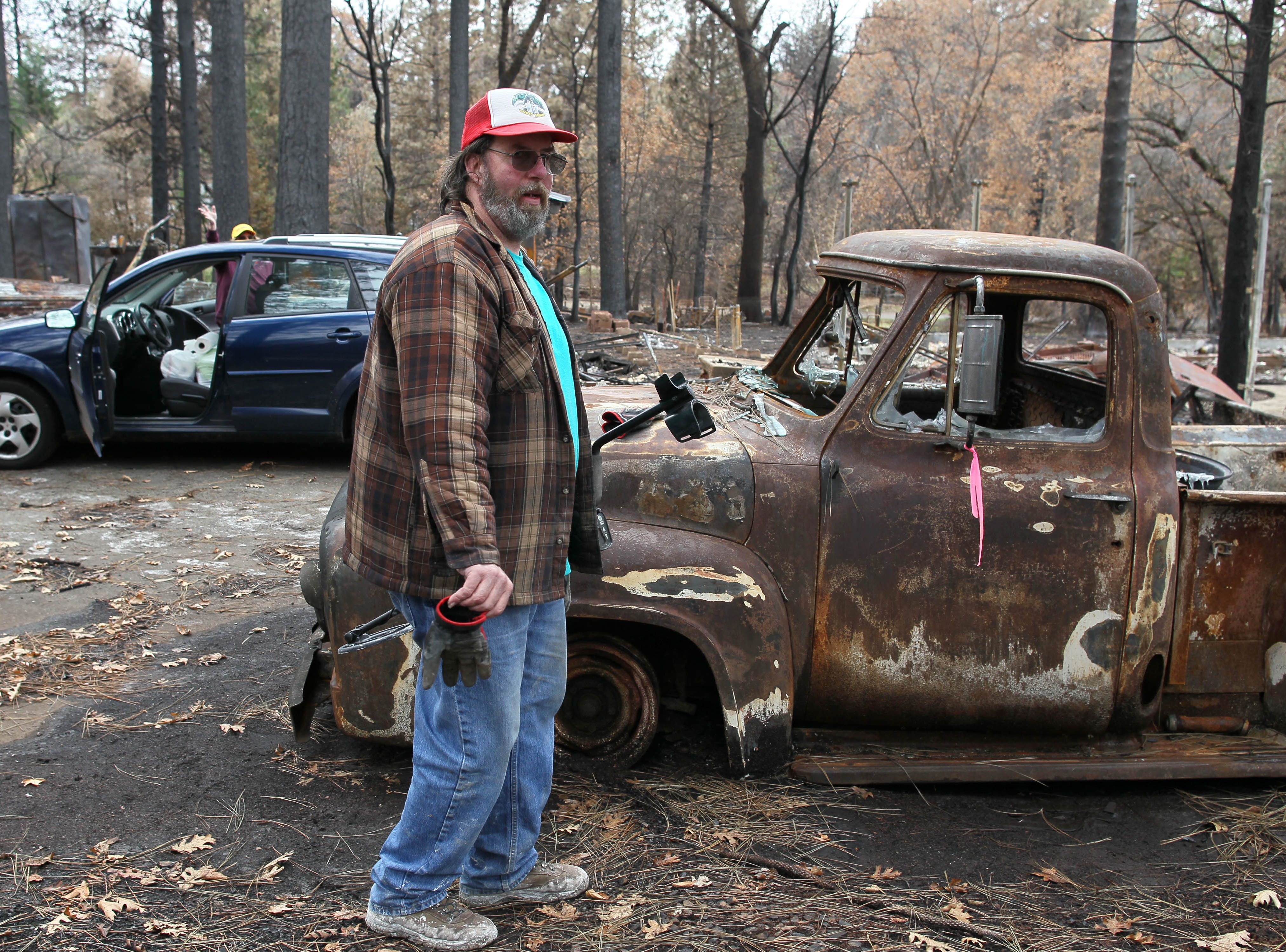 Stan Chormicle stands by his burned car. He and his wife returned to the remains of their Paradise home on Tuesday to salvage what they could.