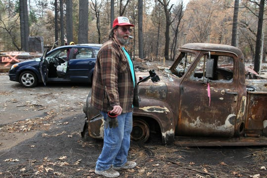 Stan Chormicle stands by his burned car in December 2018. He and his wife returned to the remains of their Paradise home on Tuesday to salvage what they could.