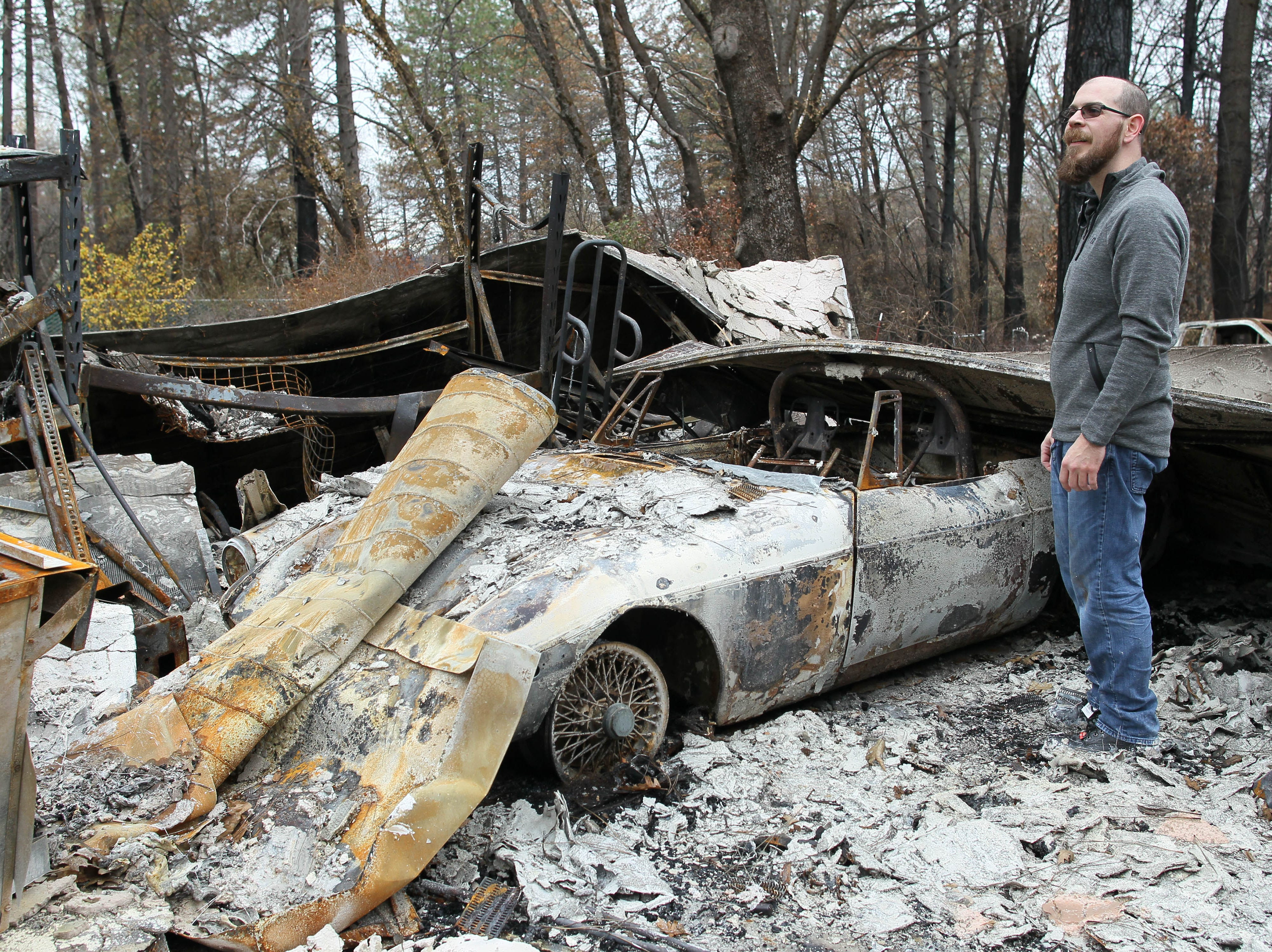 Jared Wilson stands in the ashes of his burned garage at his destroyed house in Paradise.