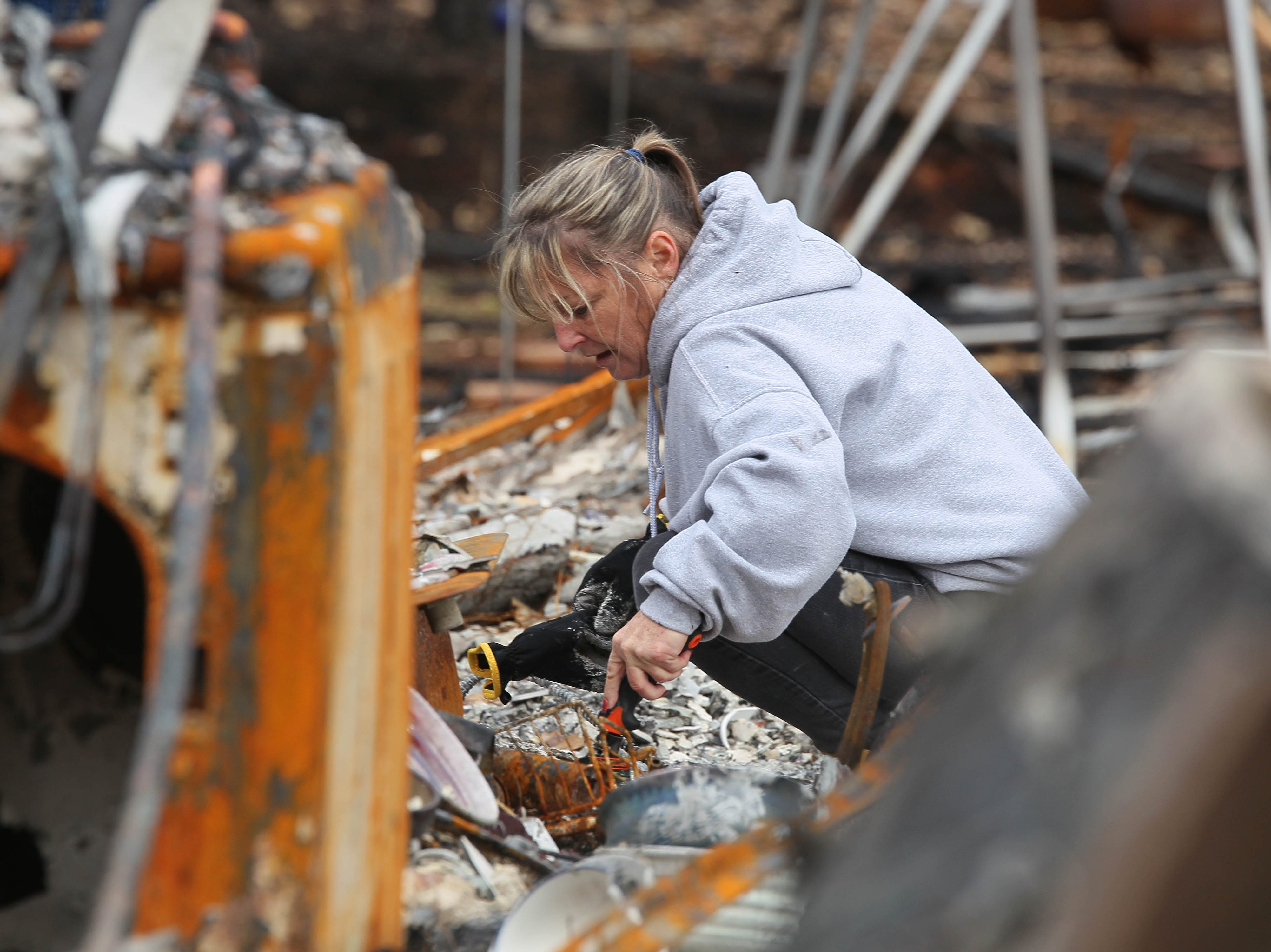 Tina Torres sifts through her burned Paradise home for any salvageable items. Tuesday was the first day she and other residents were allowed to return to their home sites since they were evacuated during the Camp Fire on Nov. 8, 2018.