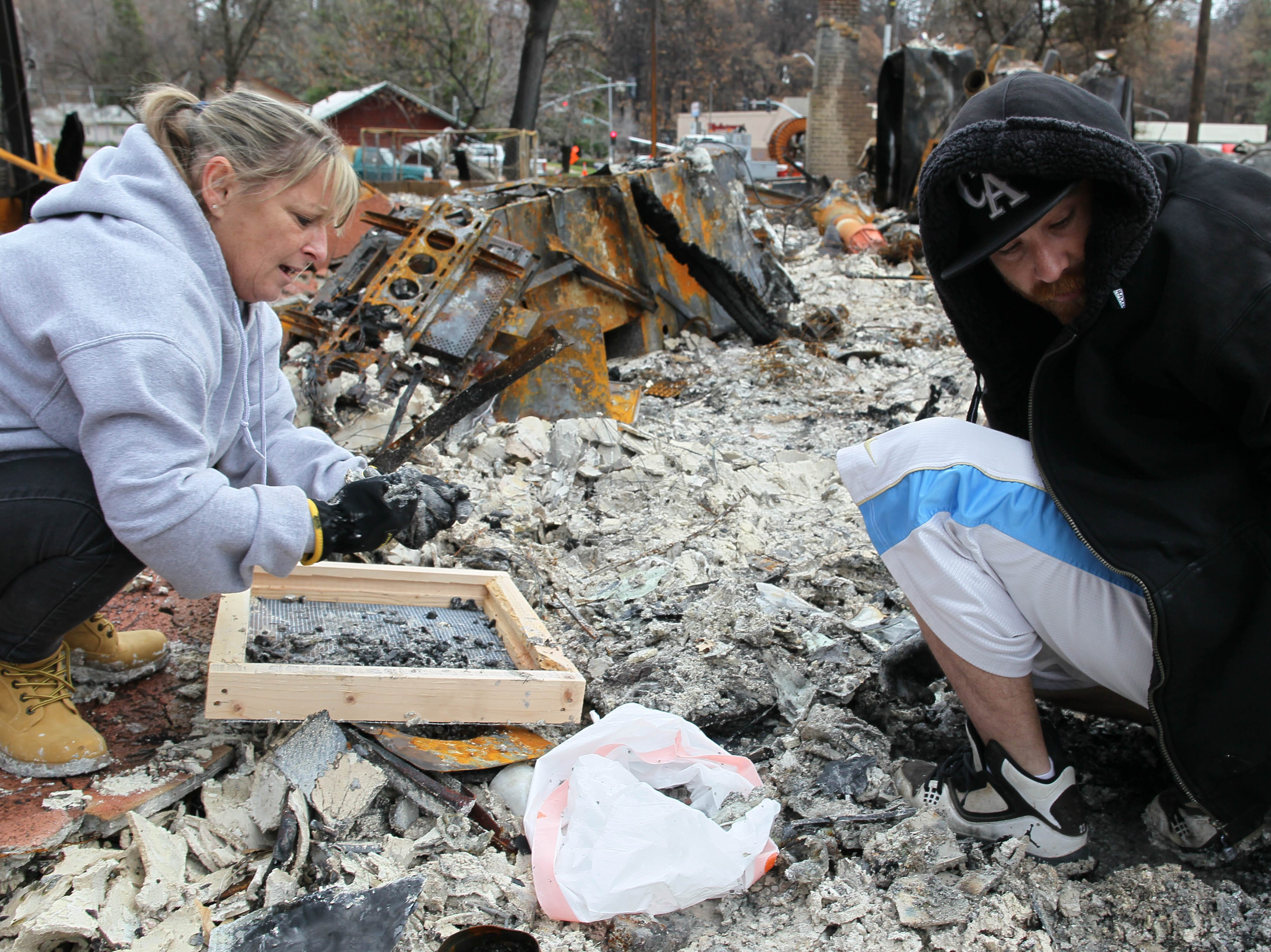 Tina Torres, left, and her daughter's friend, Brandon Duensing, sift through  debris of Torres' home, hoping to salvage items.  It's the first day she and other residents were allowed to return to their home sites since they were evacuated during the Camp Fire on Nov. 8, 2018.