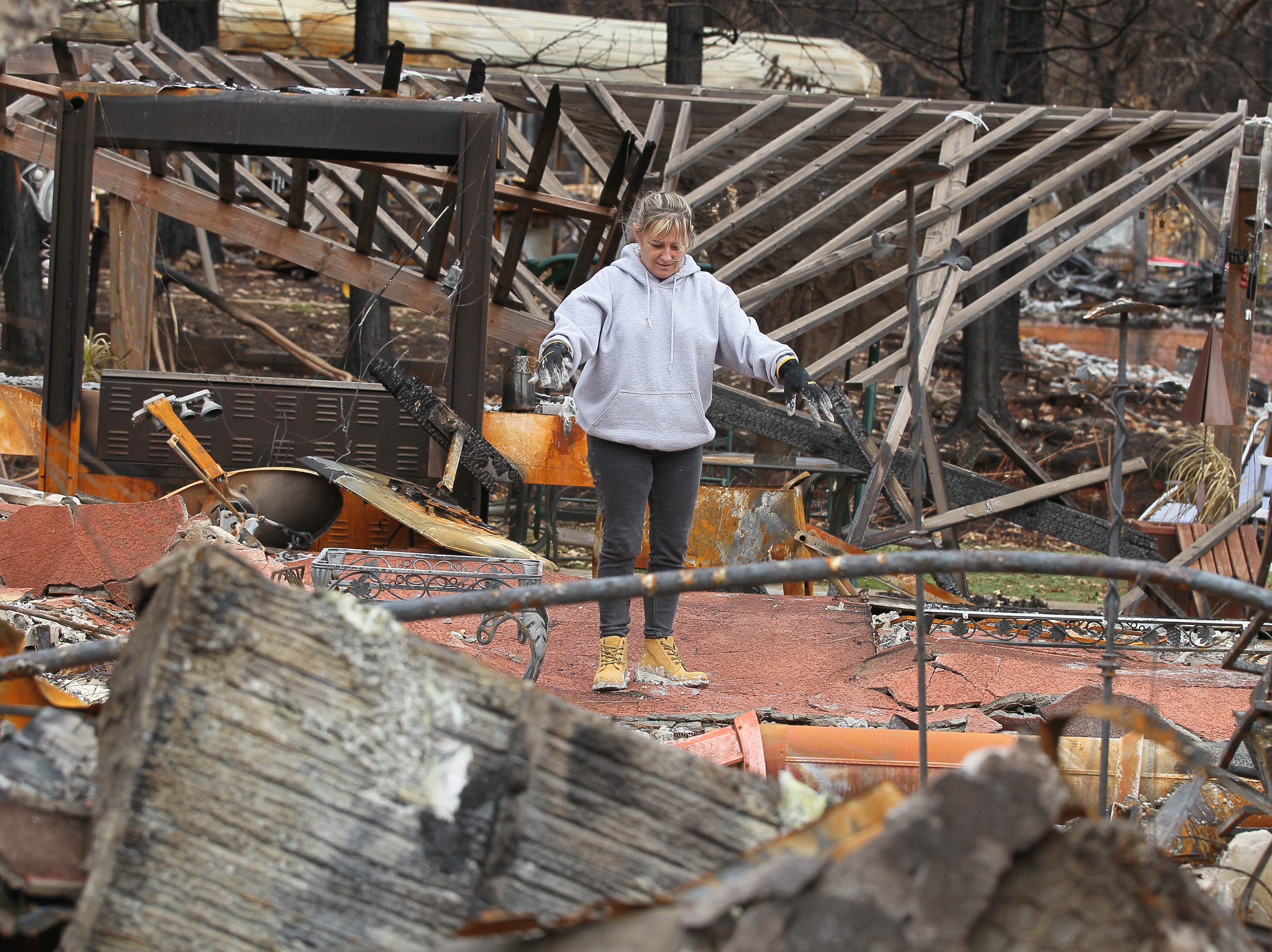 Tina Torres stands in the middle of her burned house, looking for items she can salvage. It's the first day she and other residents were allowed to return to their home sites since they were evacuated during the Camp Fire on Nov. 8, 2018.
