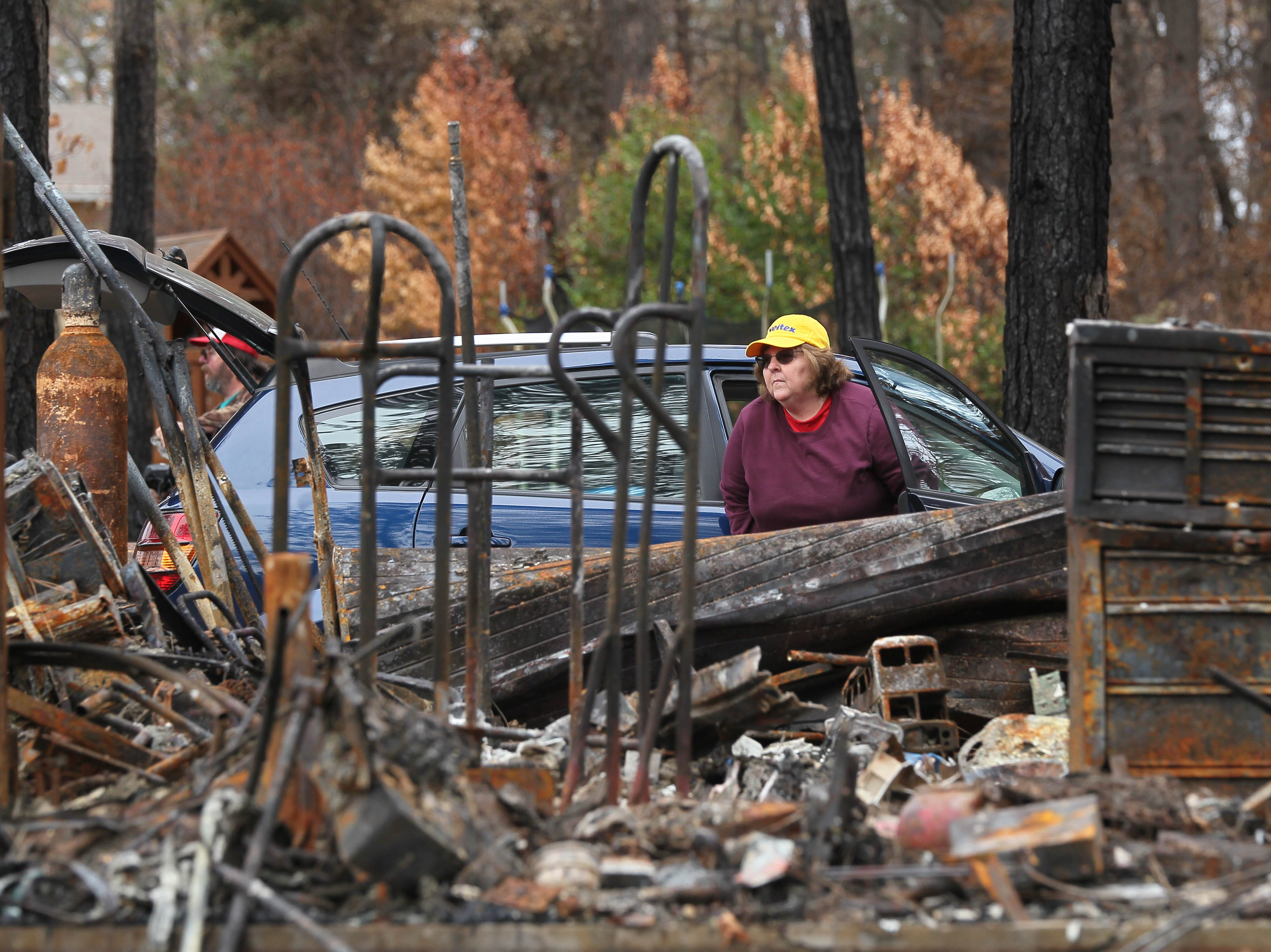 Mary Ellen Chormicle looks through debris of her burned house.