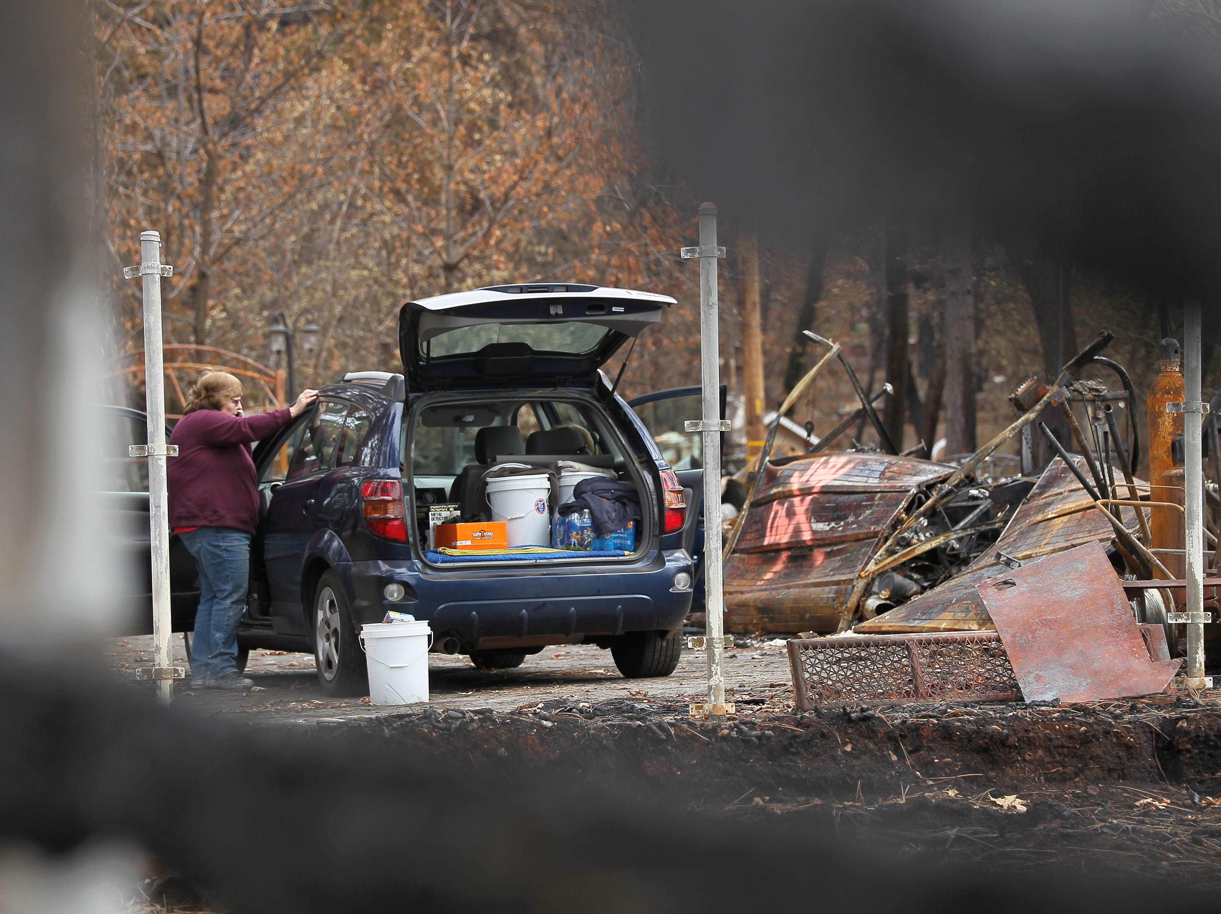 Mary Ellen Chormicle makes a phone call as she and her husband salvage items at their burned house in Paradise Tuesday.