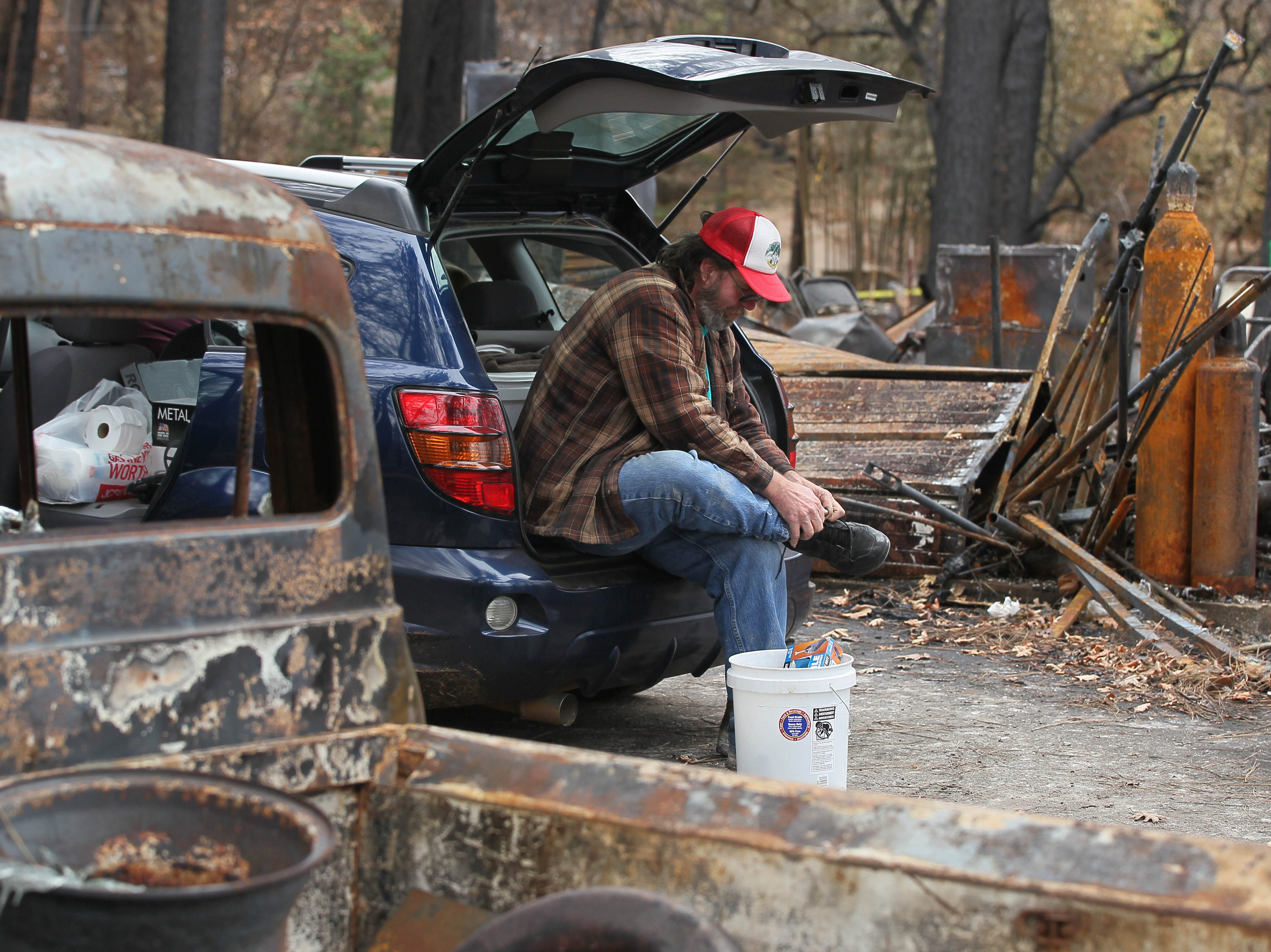 Stan Chormicle changes his shoes in the back of his car after he and his wife salvage items at his burned house in Paradise.