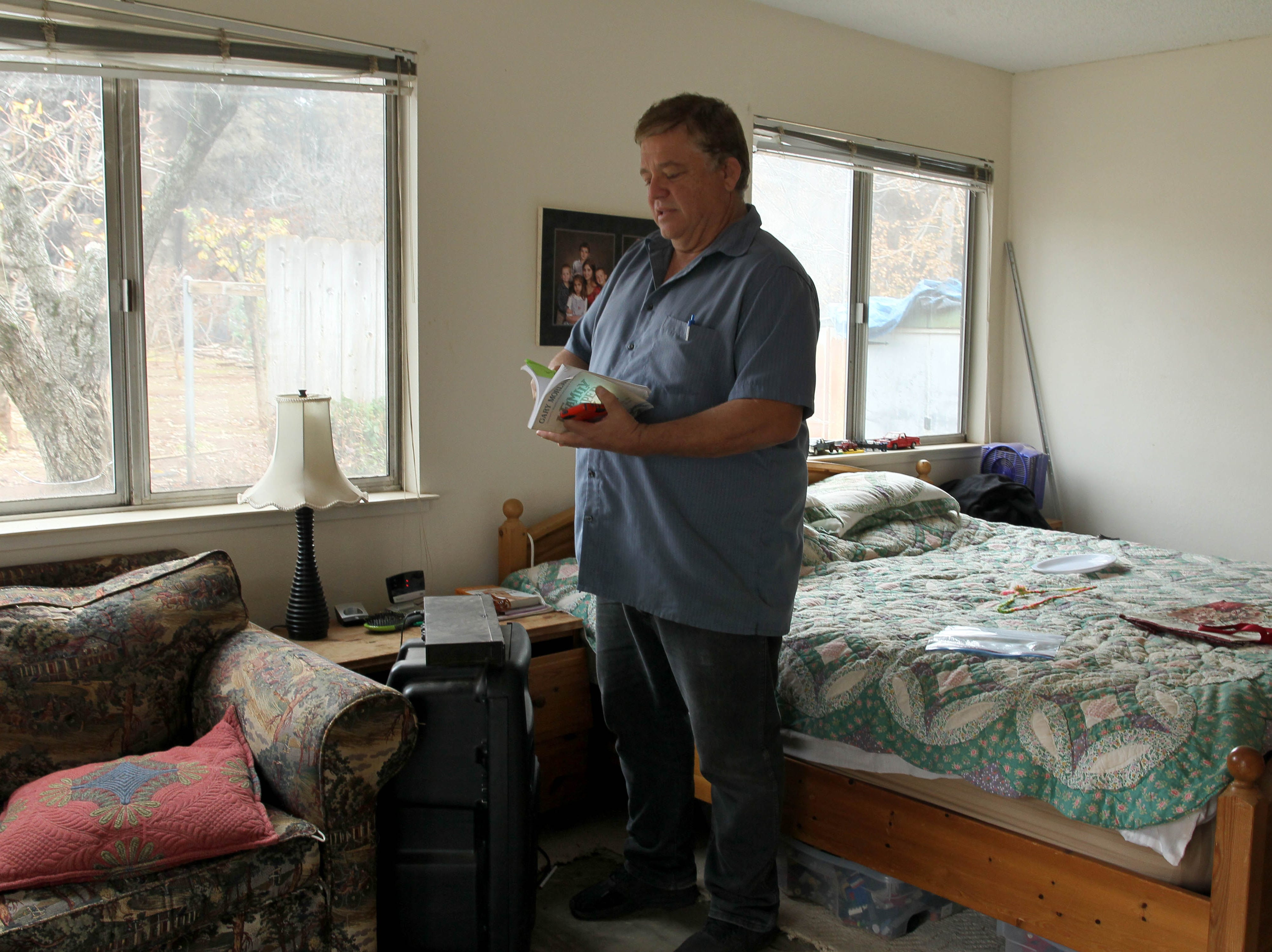Greg Barron salvages items in his bedroom on Tuesday.  The house was spared from the Camp Fire. Barron plans to remodel the house when things settle down.