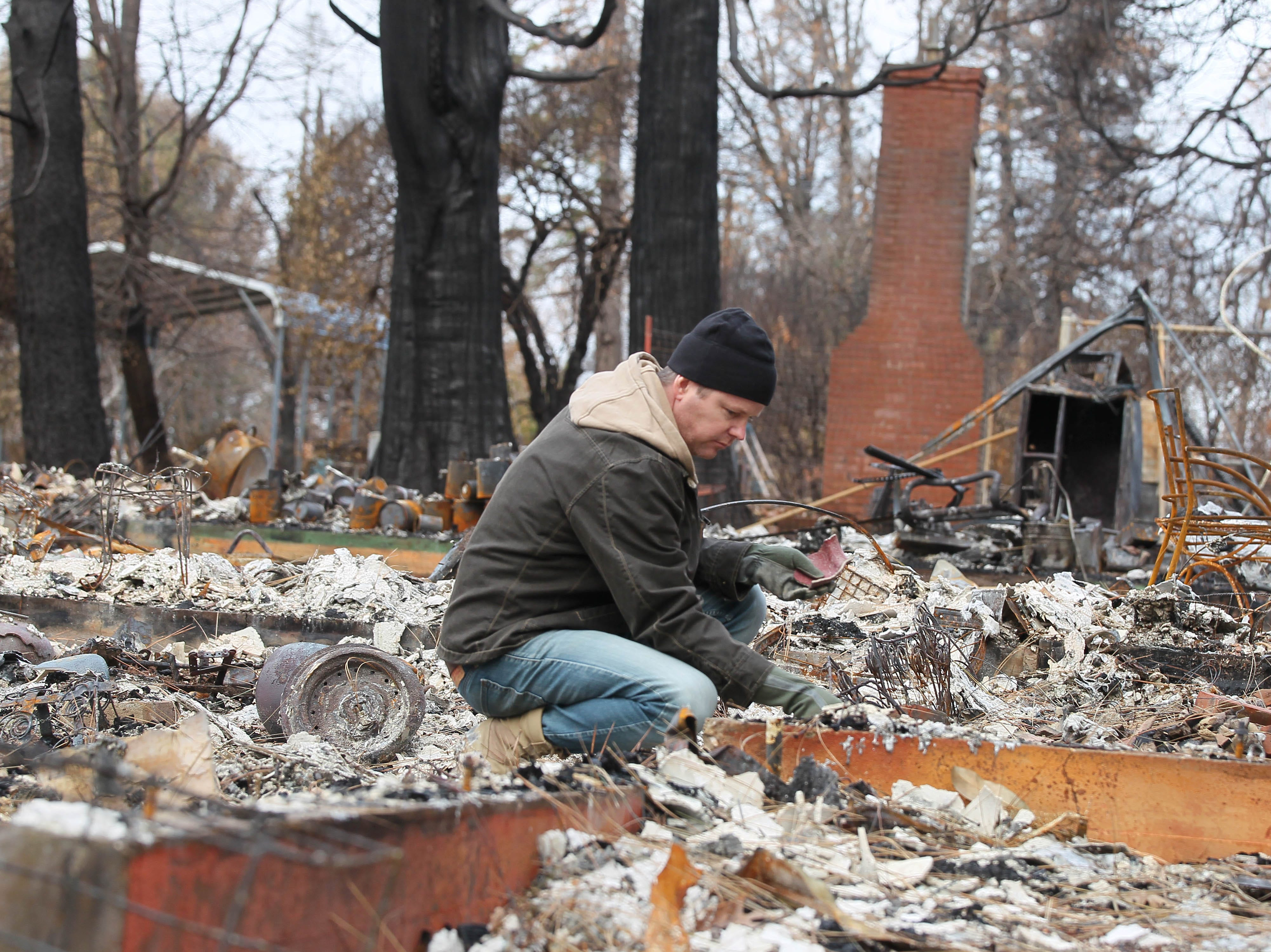 Zack Smith sifts through the debris of his parents' house along Oliver Road on Tuesday, the first day he and other Paradise residents were allowed to return since they were evacuated during the Camp Fire on Nov. 8, 2018.