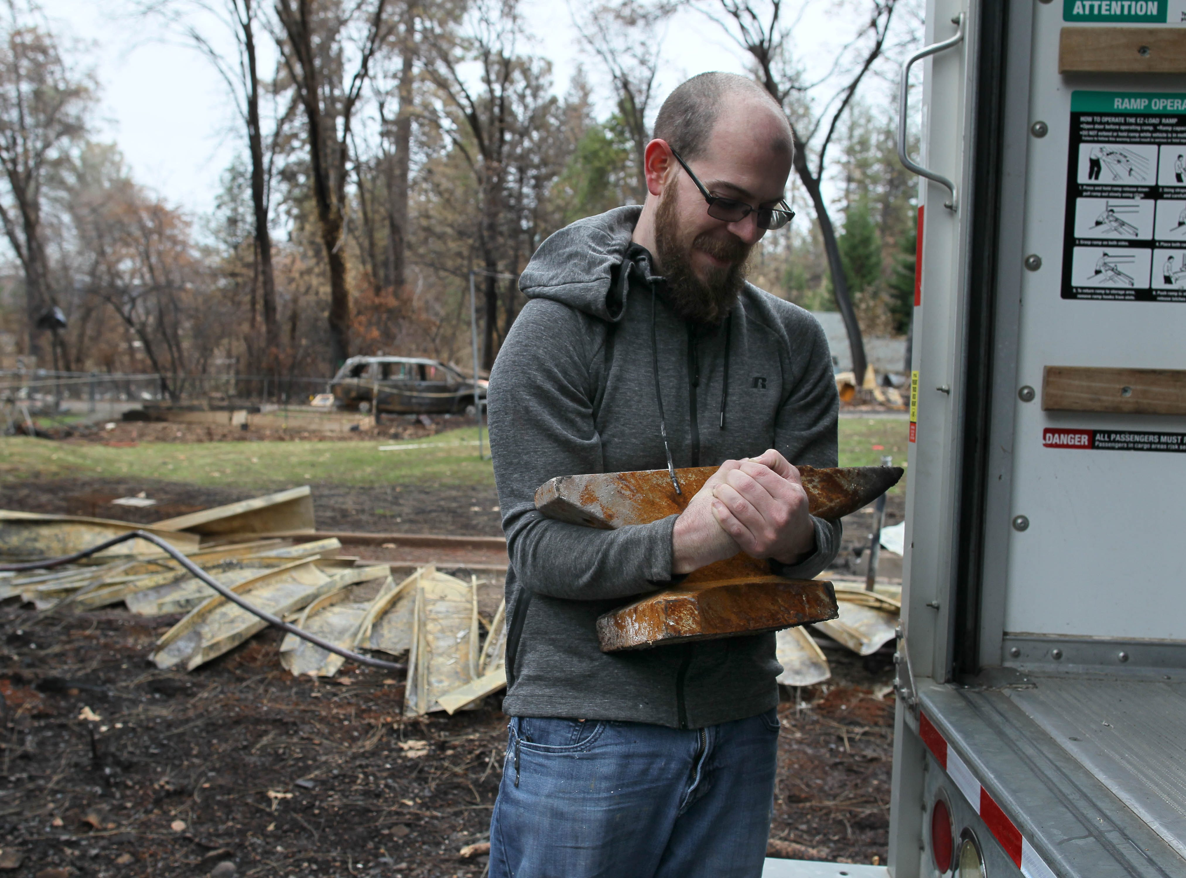 Jared Wilson carries an anvil he salvaged from his burned Paradise house to his rental truck on Tuesday. Jared and his wife returned to the house for the first time since they evacuated during the Camp Fire early in November.