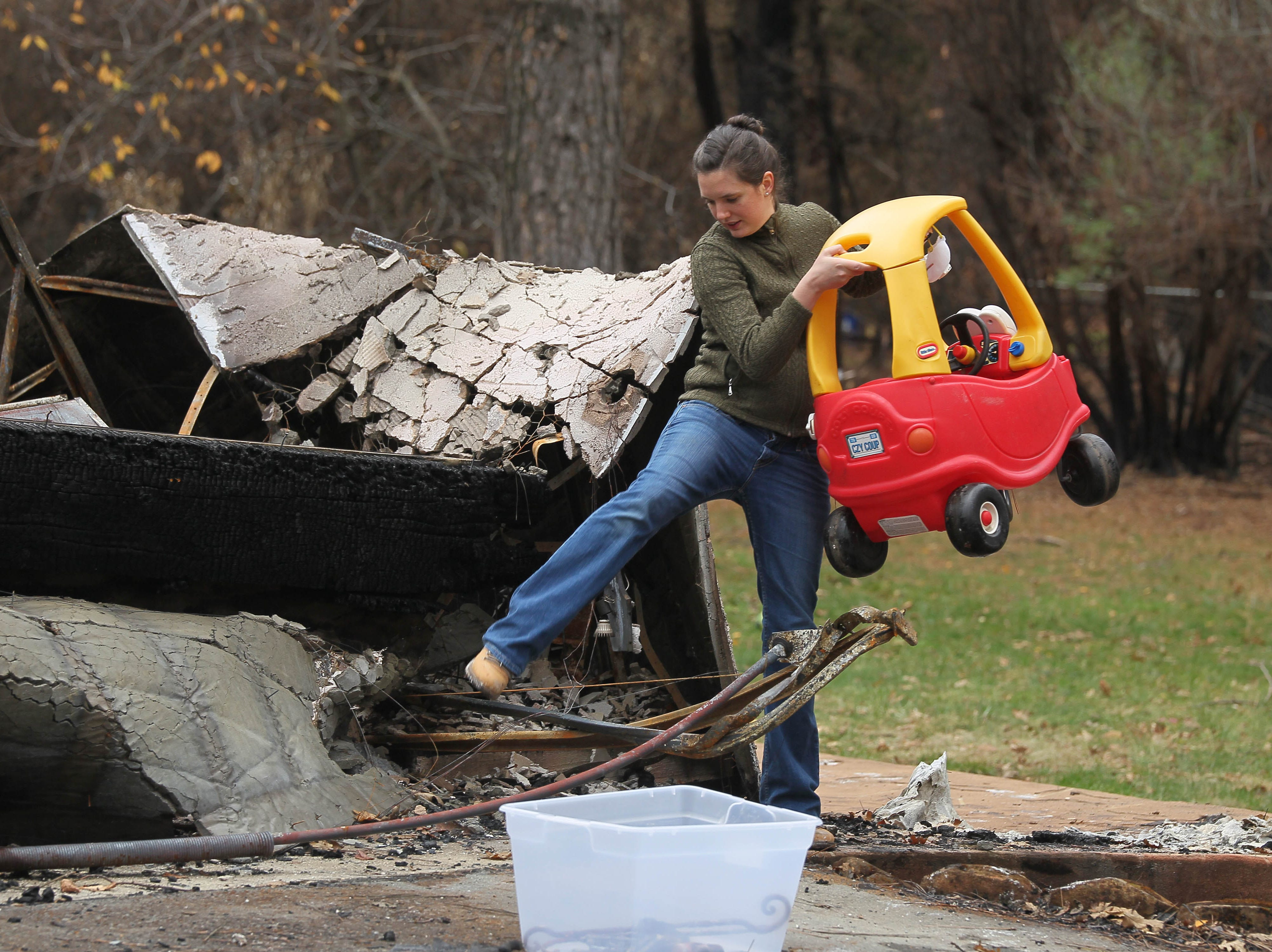 Megan Wilson salvages her son's toy car in the debris of her burned house in Paradise.