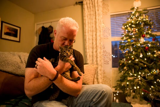 Chuck Hawley kisses Sticky, a kitten who was rescued after being glued to the side of the road in October, in his Silverton home on Monday, Dec. 17, 2018.