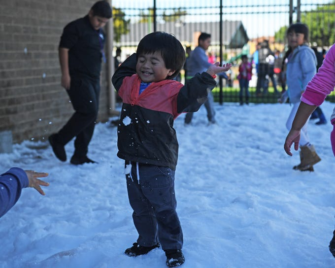 A boy tosses snow in the courtyard of the Cesar Chavez library Wednesday afternoon.