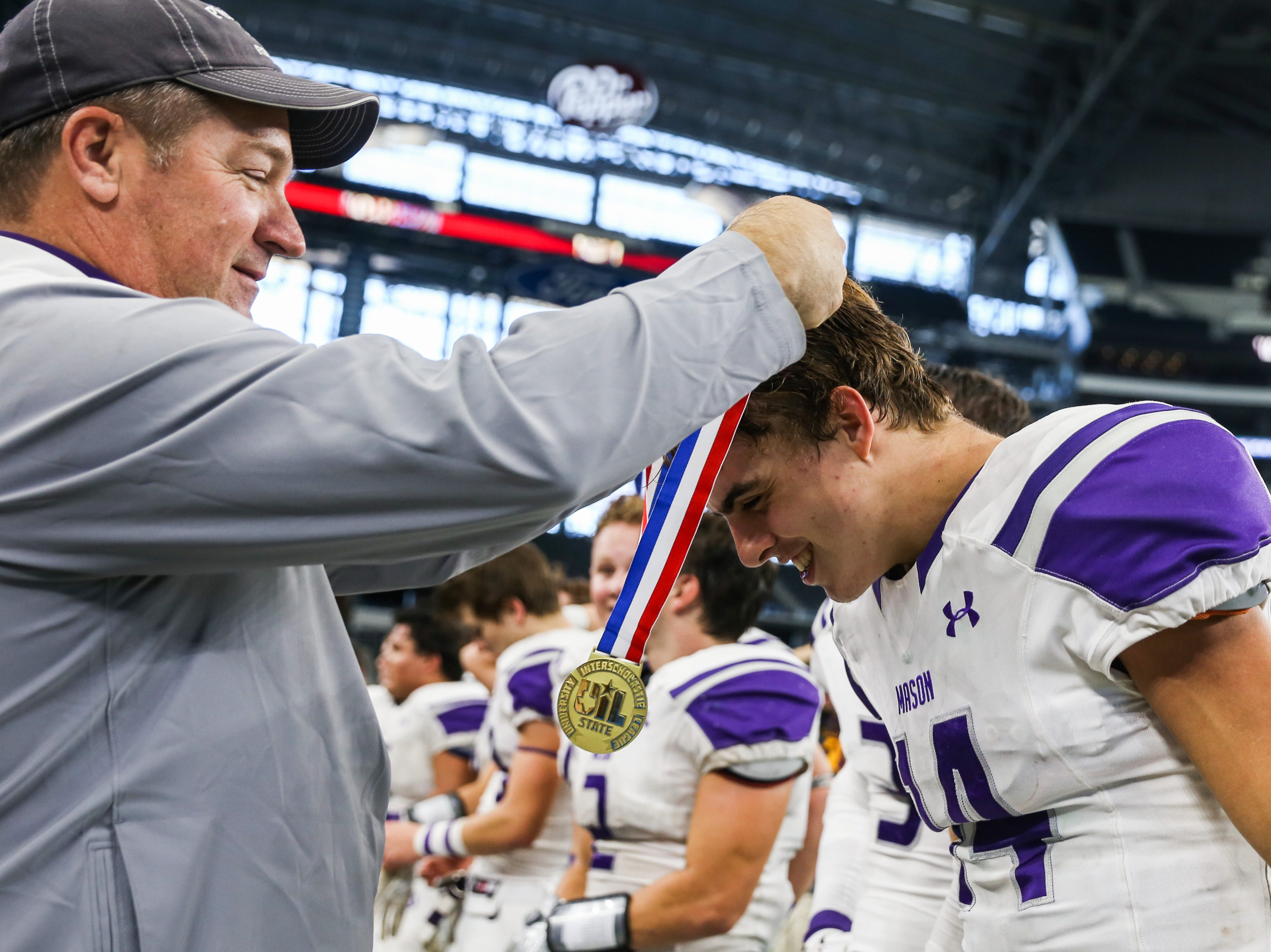 A championship metal is put around Mason's Otto Wofford after the victory over New Deal Thursday, Dec. 20, at the AT&T Stadium.