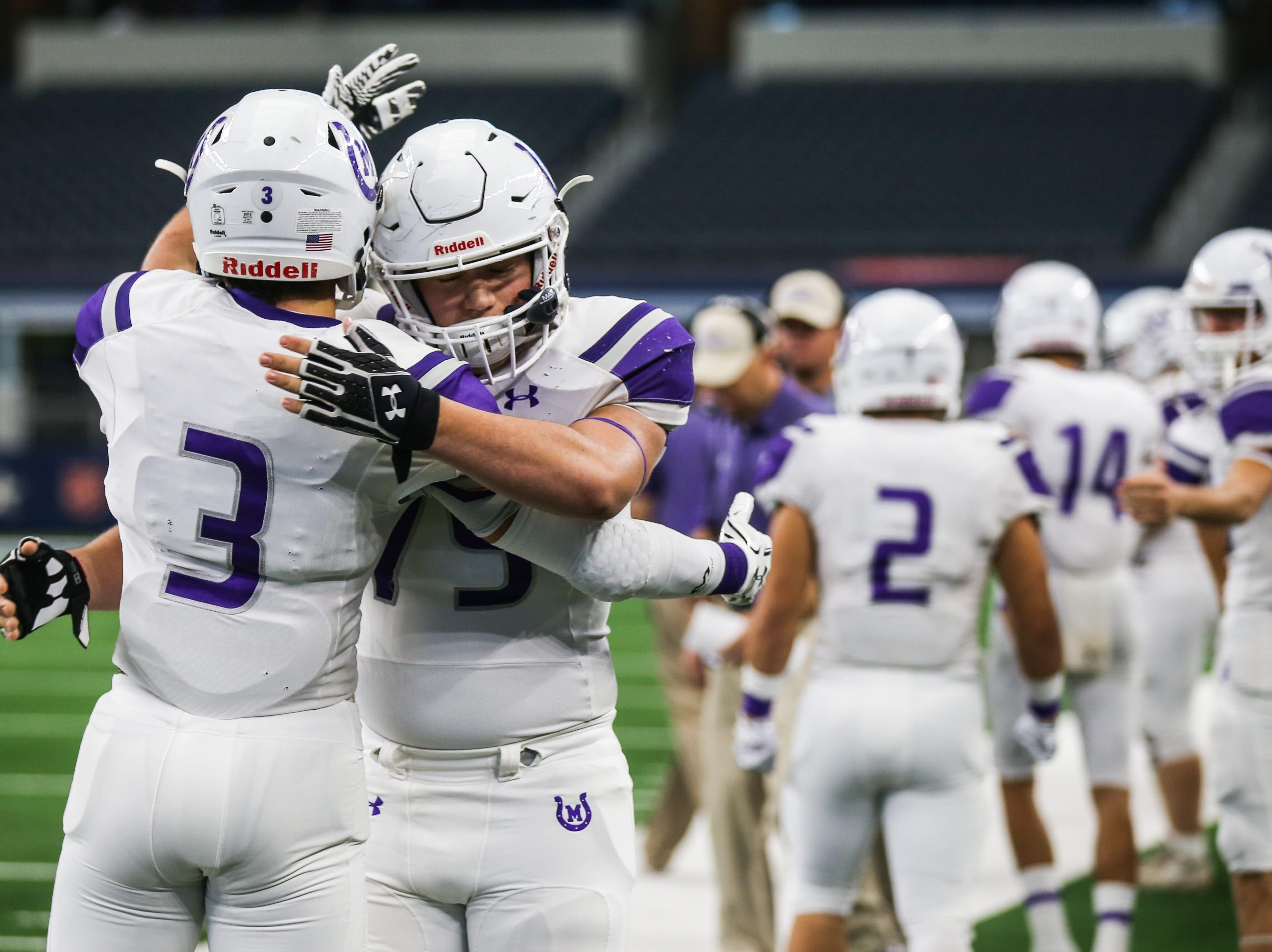 Mason players cheer each other on before the state finals game against New Deal Thursday, Dec. 20, at the AT&T Stadium.