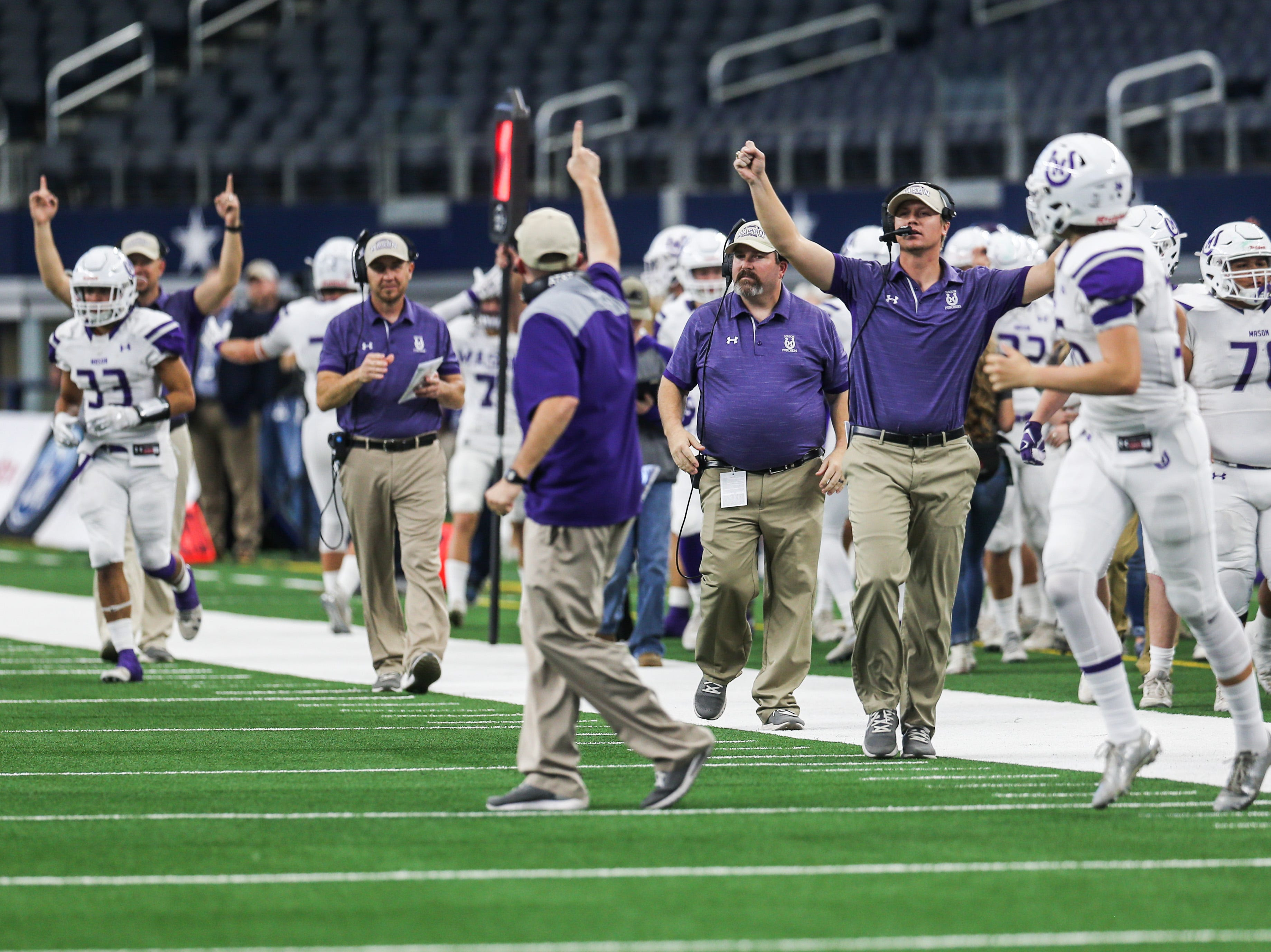 Mason coaches cheer after a touchdown during the state finals game against New Deal Thursday, Dec. 20, at the AT&T Stadium.