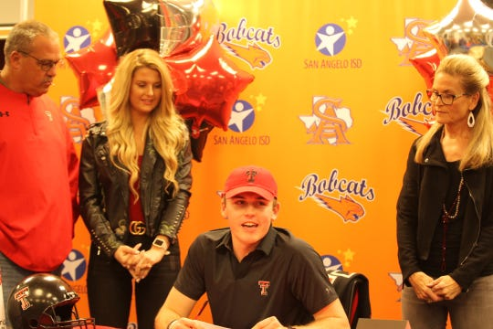 San Angelo Central High School quarterback Maverick McIvor is all smiles while surrounded by family after signing a letter of intent with Texas Tech University on Wednesday, Dec. 19, 2018.