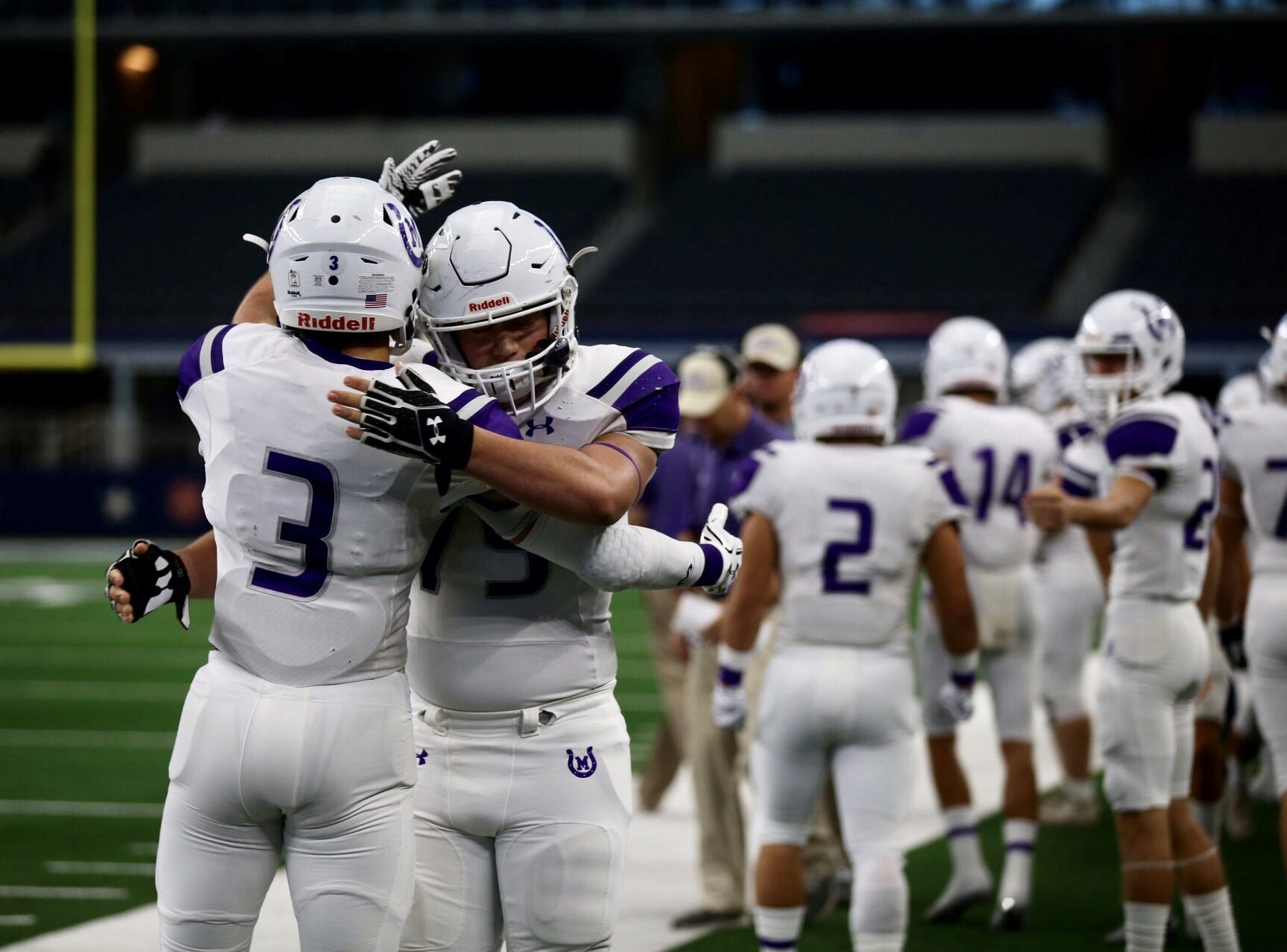Mason Punchers teammates hug before taking on the New Deal Lions during the Class 2A Division I football state final Thursday, Dec. 20, 2018 at AT&T Stadium in Arlington.