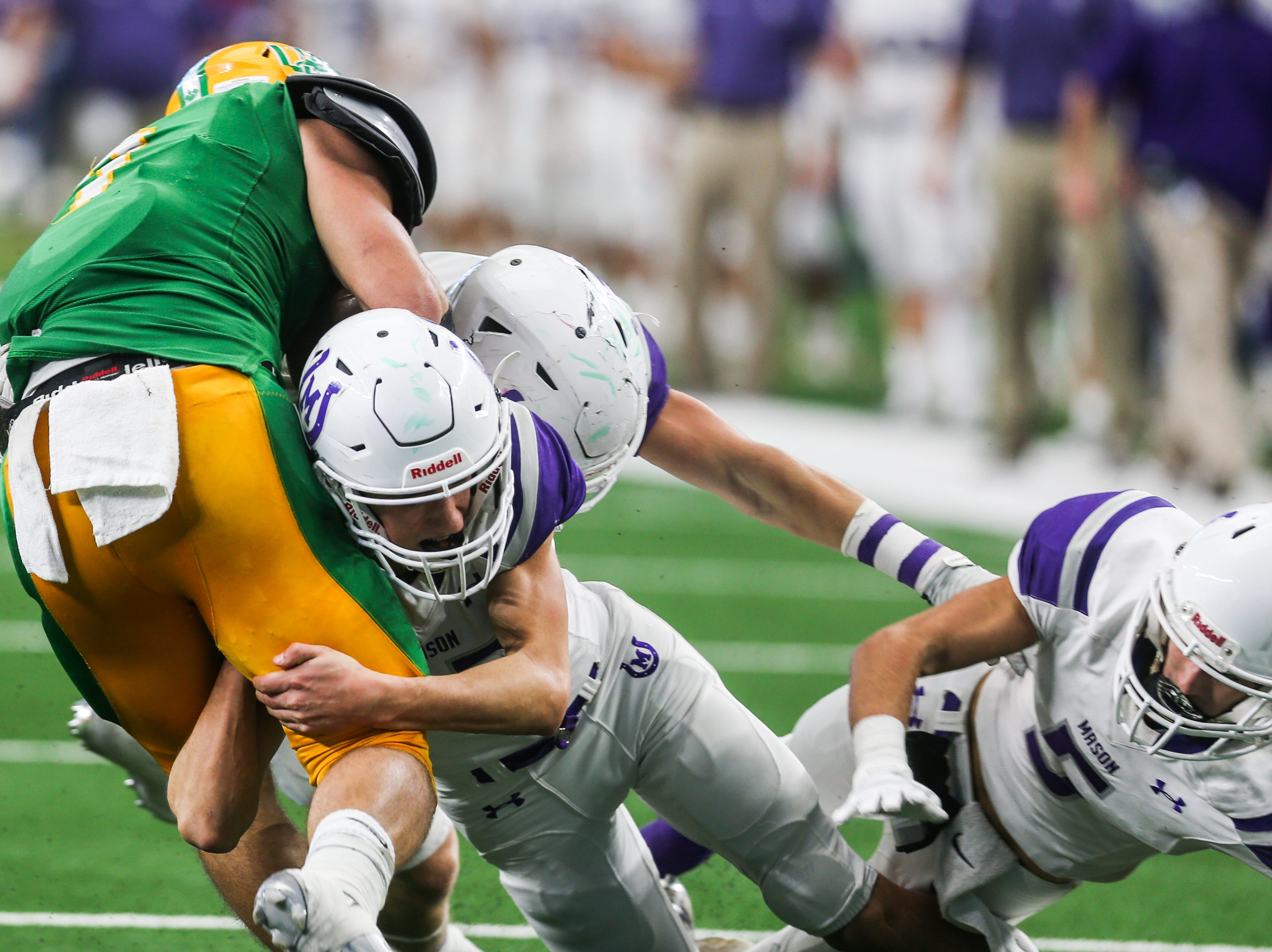 Mason defense tackle New Deal ball carrier during the state finals game against New Deal Thursday, Dec. 20, at the AT&T Stadium.