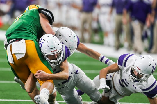 Mason defenders tackle a New Deal ball carrier during the state final Thursday, Dec. 20, 2018, at AT&T Stadium.