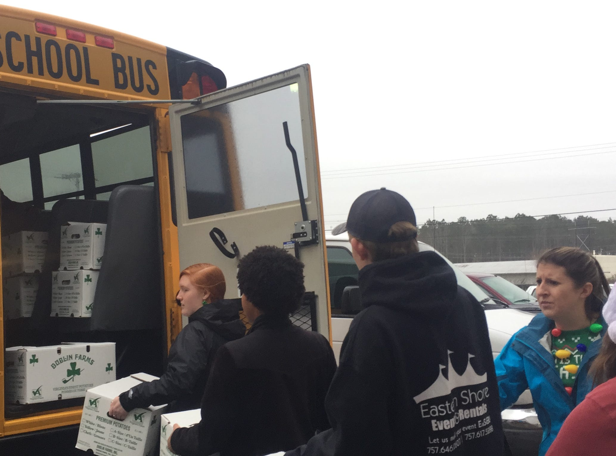 Northampton High School Honor Society members load into a school bus some of the 200 boxes of food being delivered to Eastern Shore of Virginia residents for the Eastern Shore News' 58th Annual Bank of Cheer campaign in Tasley, Virginia on Thursday, Dec. 20, 2018.
