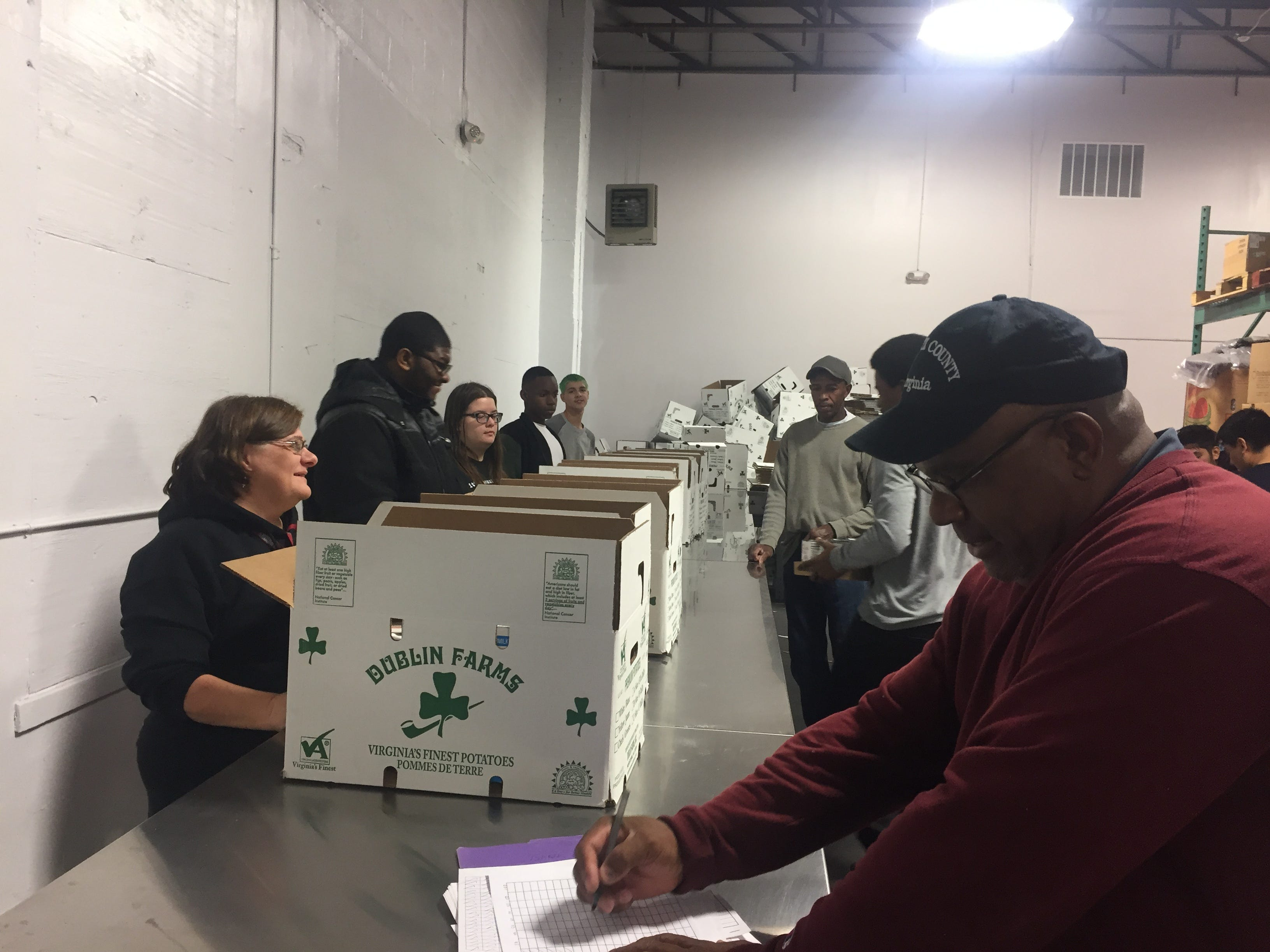 Nandua High School band members and band director Kendra Powell, with the help of John Smith, right, of the Accomack County Department of Parks and Recreation, pack boxes of food for the Eastern Shore News' 58th Annual Bank of Cheer in Tasley, Virginia on Wednesday, Dec. 19, 2018.