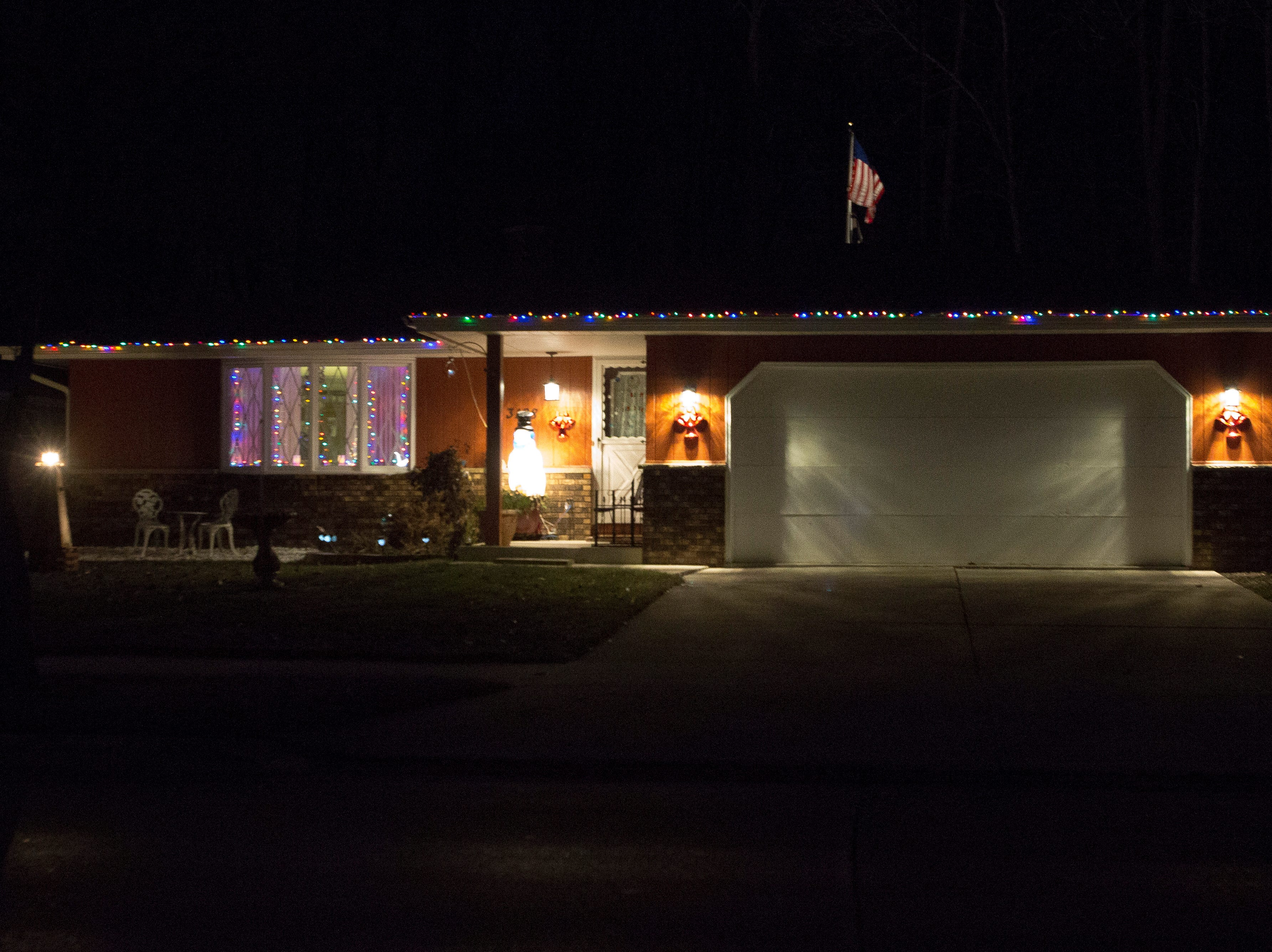 The U.S. flag shows from behind a holiday decorated home, Wednesday, December 19, 2018, in Sheboygan, Wis.
