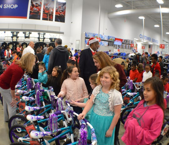 Caddo Parish District Attorney James E. Stewart Sr. (wearing Santa hat) mingles with Caddo Parish elementary students receiving Christmas gift bicycles at Academy Sports and Outdoors Wednesday.