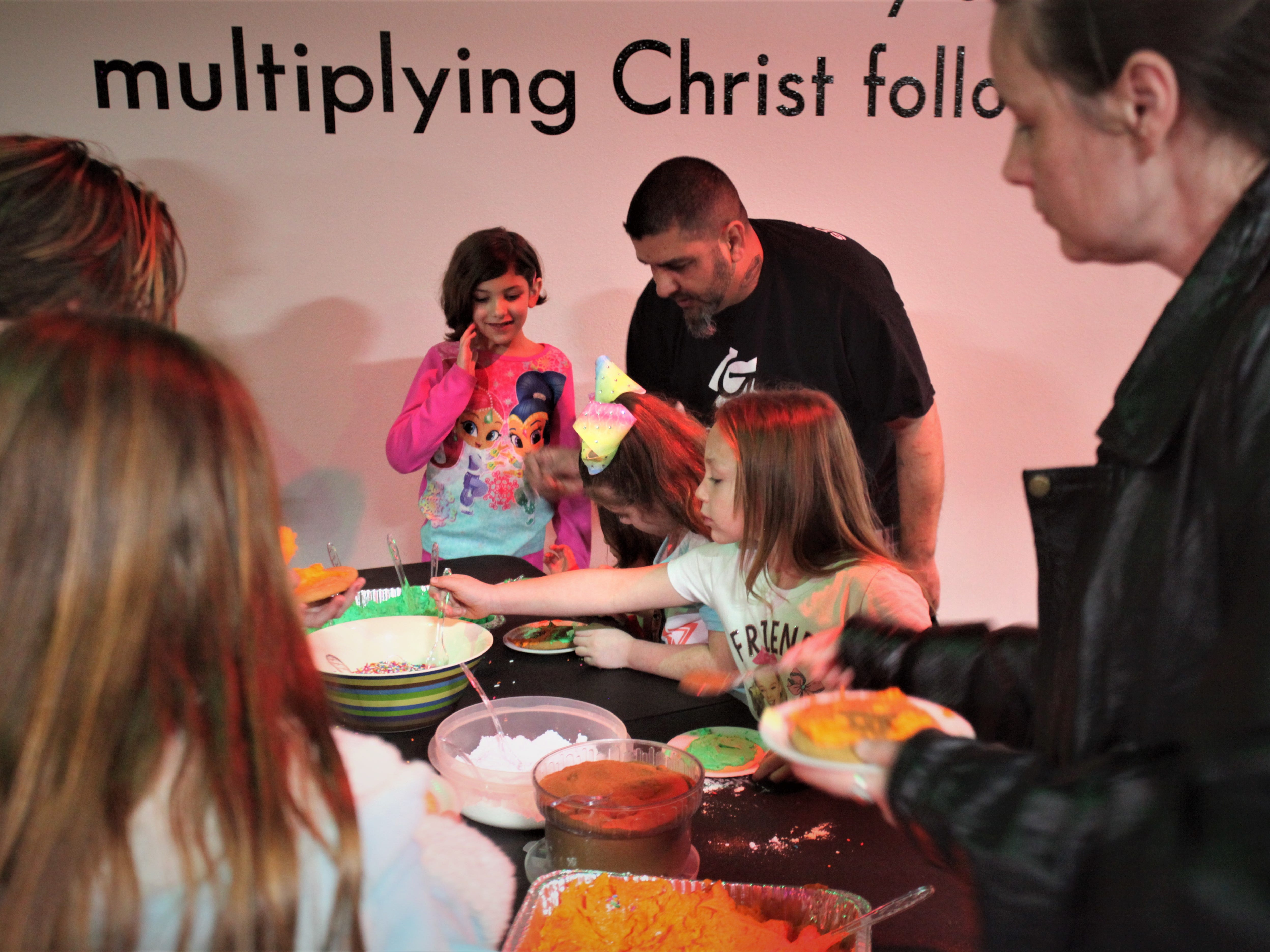 Families decorate cookies during a Christmas PJ and Movie Night at Jesus Was Homeless Dec. 19.