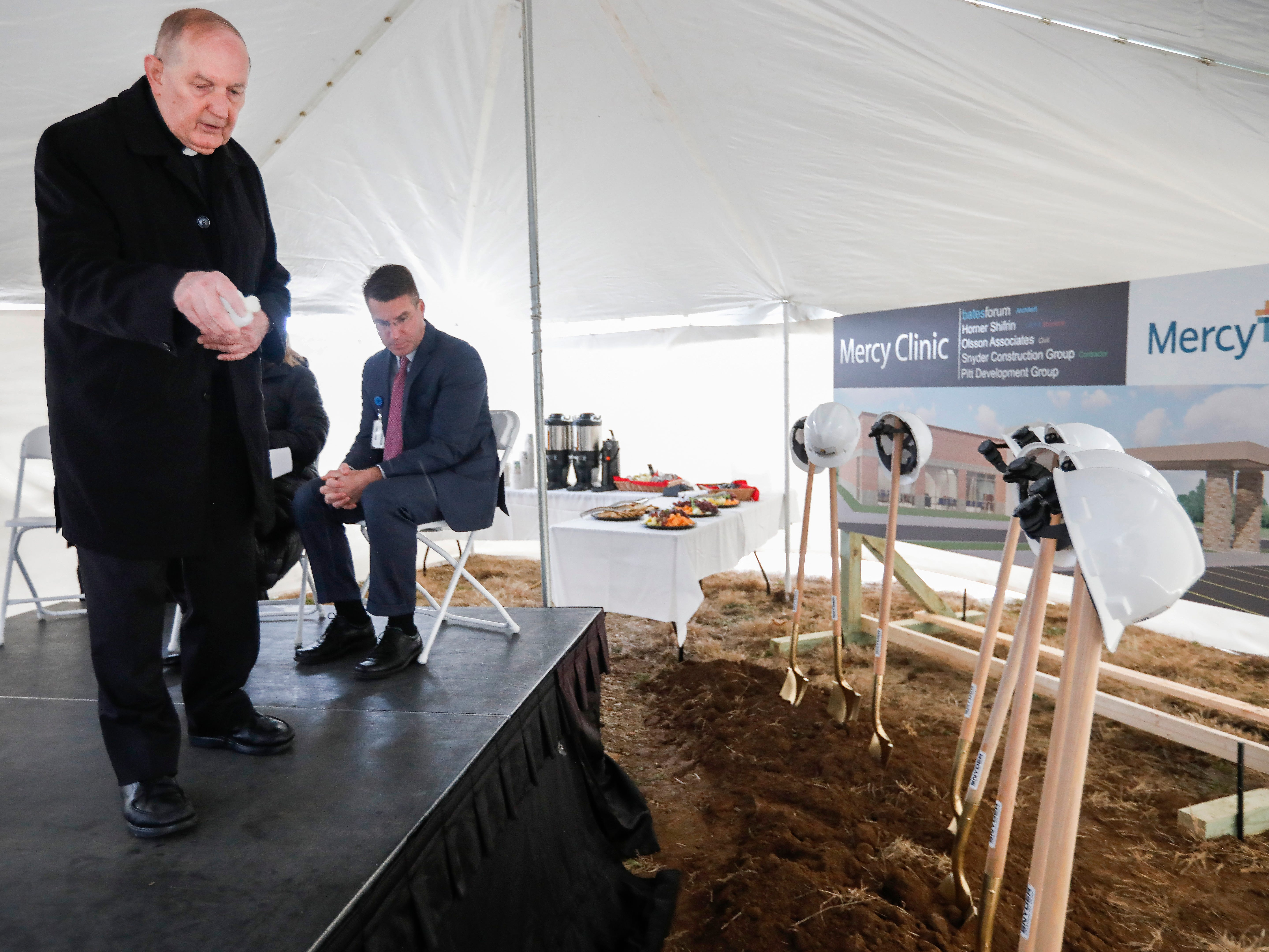 Msgr. Tom Reidy blesses the ground with holy water during a groundbreaking ceremony for the new Mercy clinic which will be located at Republic Road and Scenic Avenue.