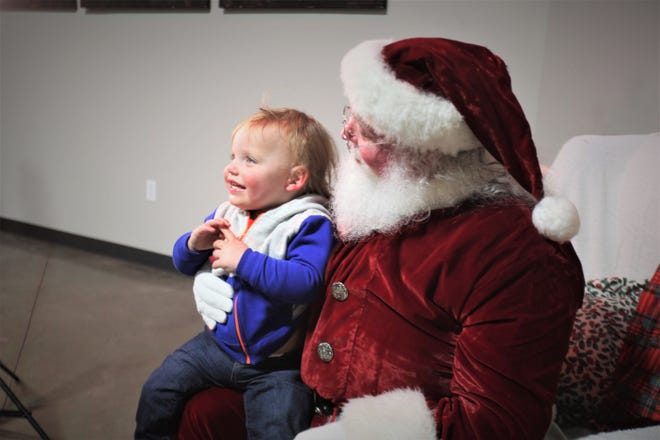"Mark ""Santa"" Donner holds Waylon Moss during the Jesus Was Homeless Christmas PJ and Movie Night."