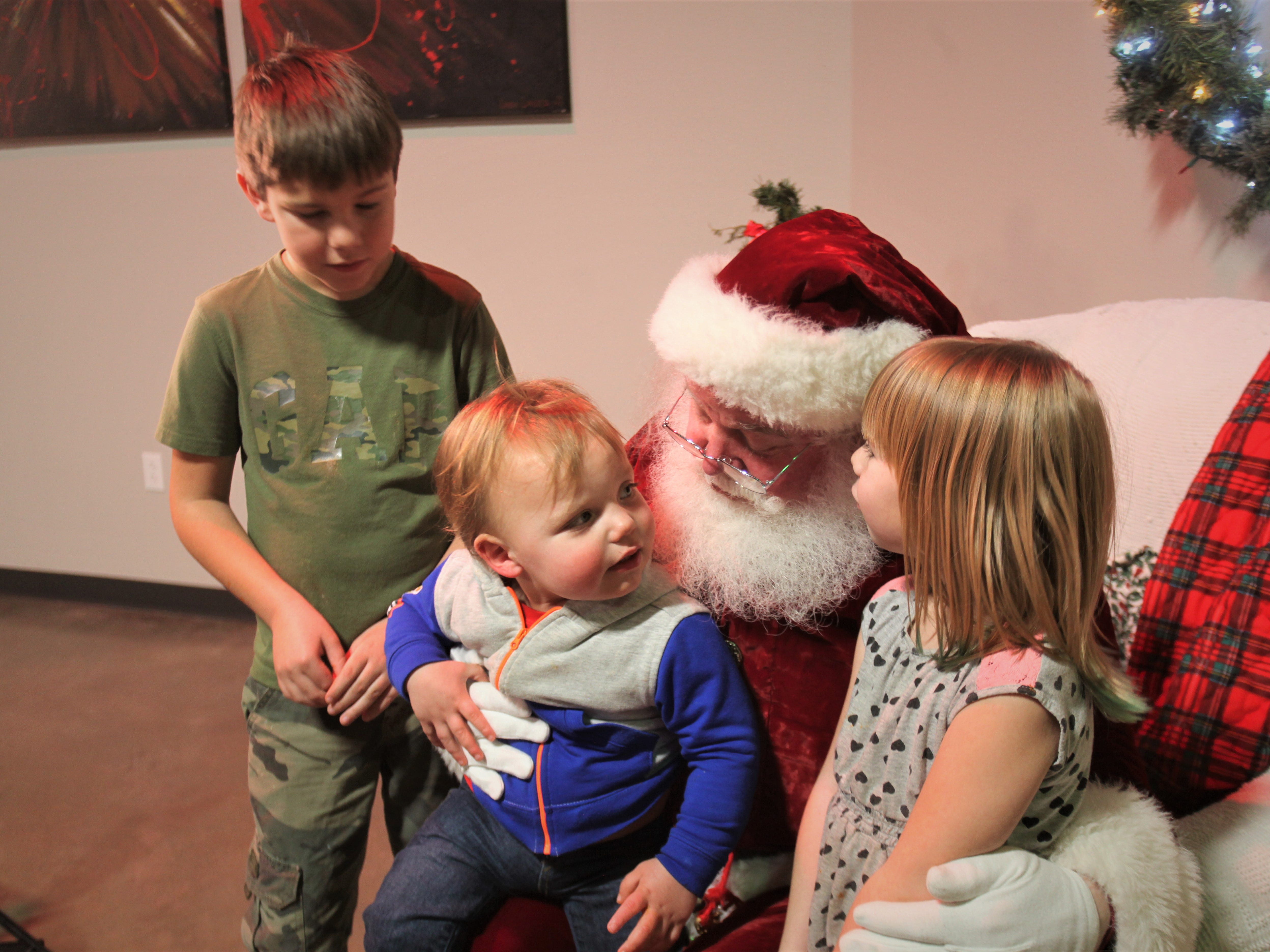 """Mark """"Santa"""" Donner speaks with the Moss siblings, Shelby, from left, Waylon and Symphany."""