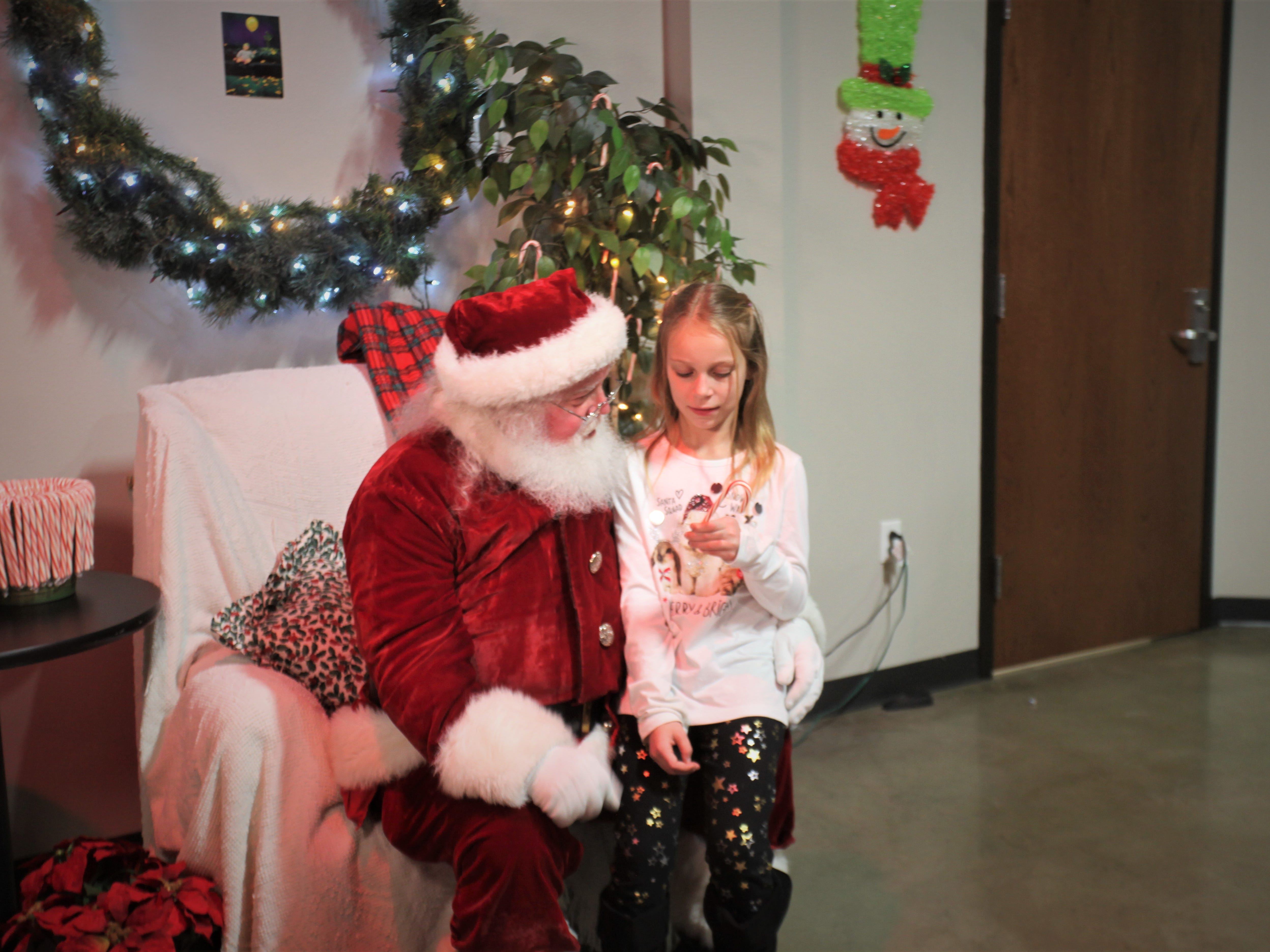 """Kaleigh Jackson, 8, discusses what she wants for Christmas with Mark """"Santa"""" Donner."""