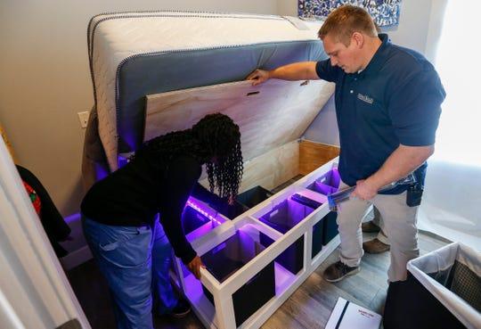 Nathan Lotz, right, and Billie Davis, of Jordan Valley, put some empty bins in storage under the bed in M.J.'s home at Eden Village on Monday, Dec. 17, 2018.