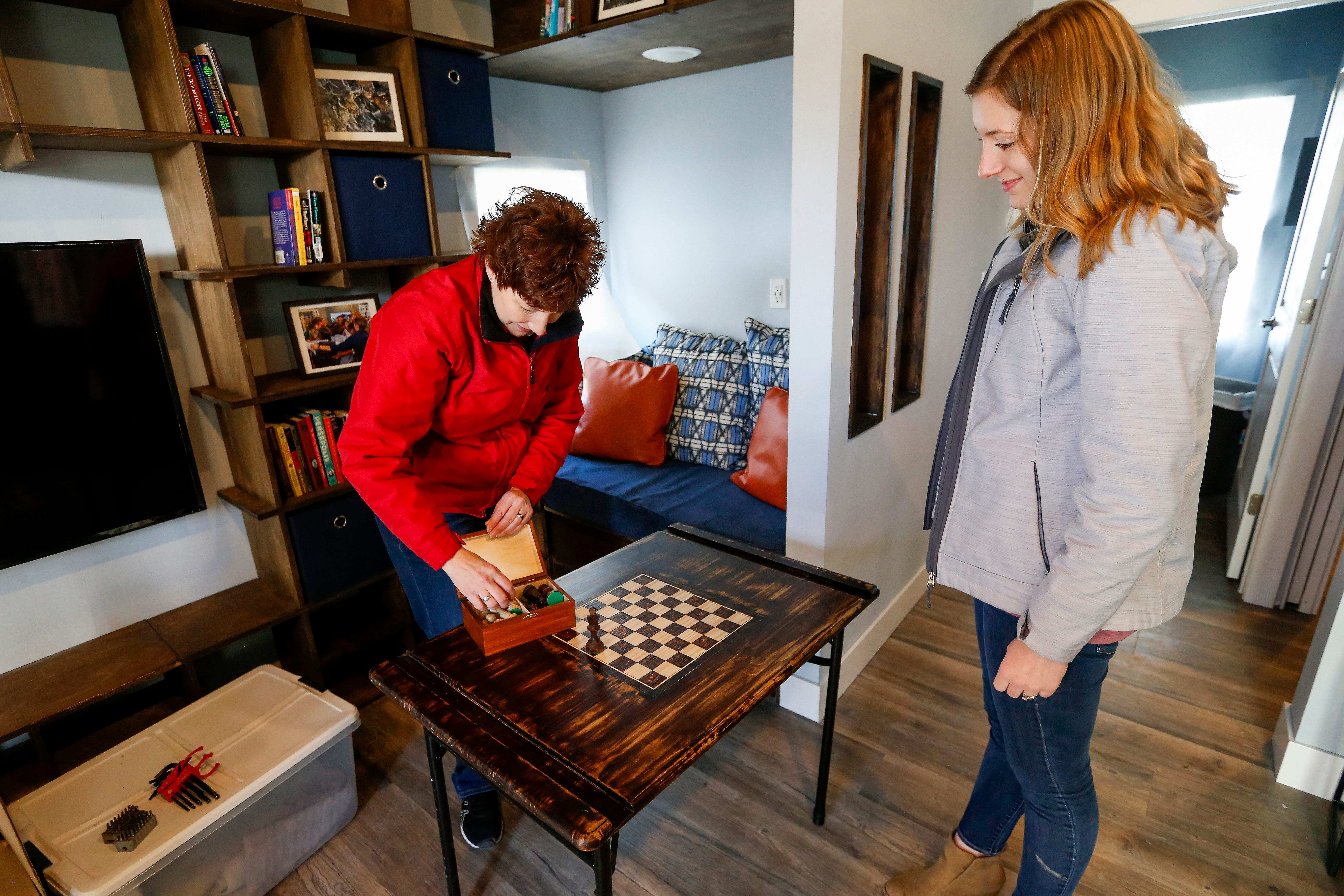 Professor Traci Sooter, left, and student Meagan Ley, of Drury, set up the table with a chess board in M.J.'s home at Eden Village on Monday, Dec. 17, 2018.