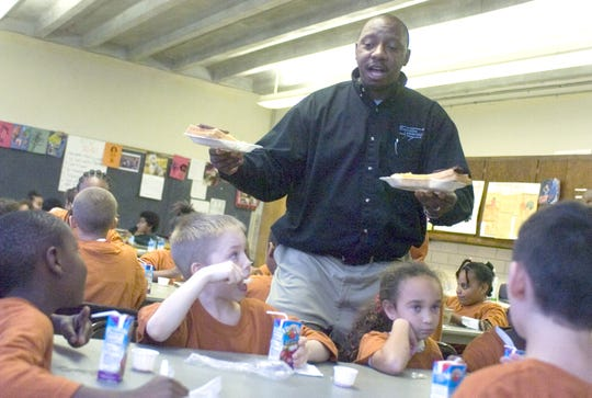 DeWayne Moore, executive director of the Boys & Girls Club of Waynesboro, Staunton and Augusta County, passes out dinners to kids during an event held at the Booker T. Washington Community Center in Staunton In this November 2006 photo. Moore is now assistant principal at Robert E. Lee High School.