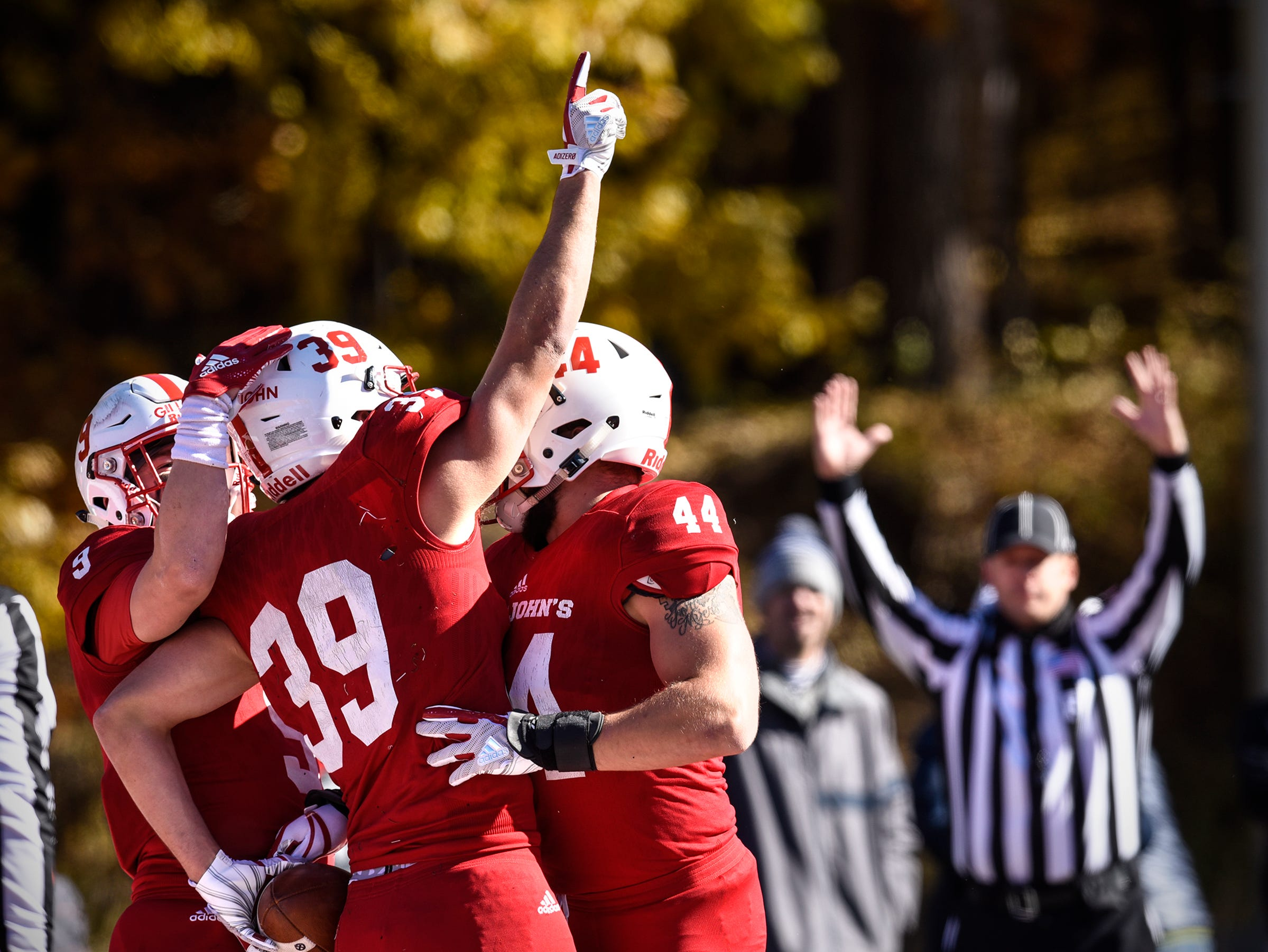Tommy Auger raises his hand skyward in tribute to coach John Gagliardi after scoring a touchdown during the first half of the Saturday, Oct. 20, game against St. Olaf at Clemens Stadium in Collegeville