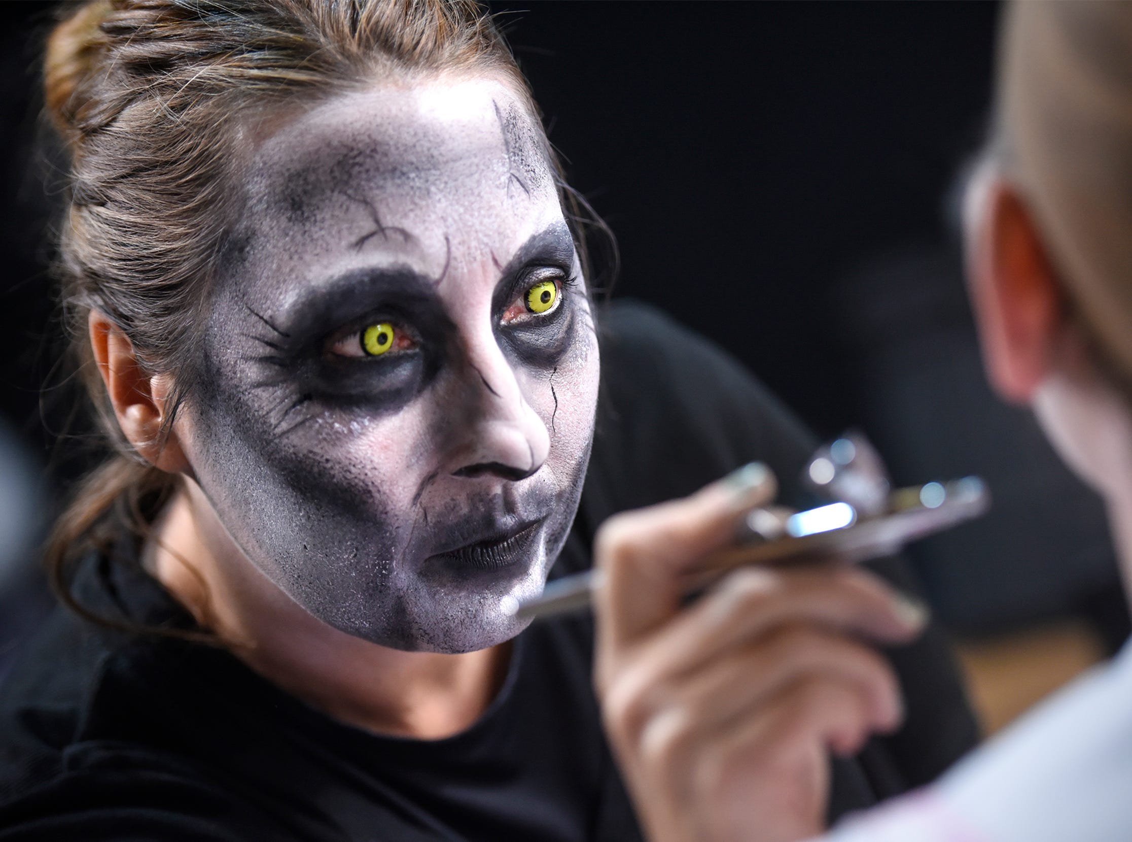 Beth Reimer uses an airbrush while applying makeup on performers Thursday, Oct. 18, at Molitor's Haunted Acres in Sauk Rapids. This year marks the 21st season of the haunted attraction.