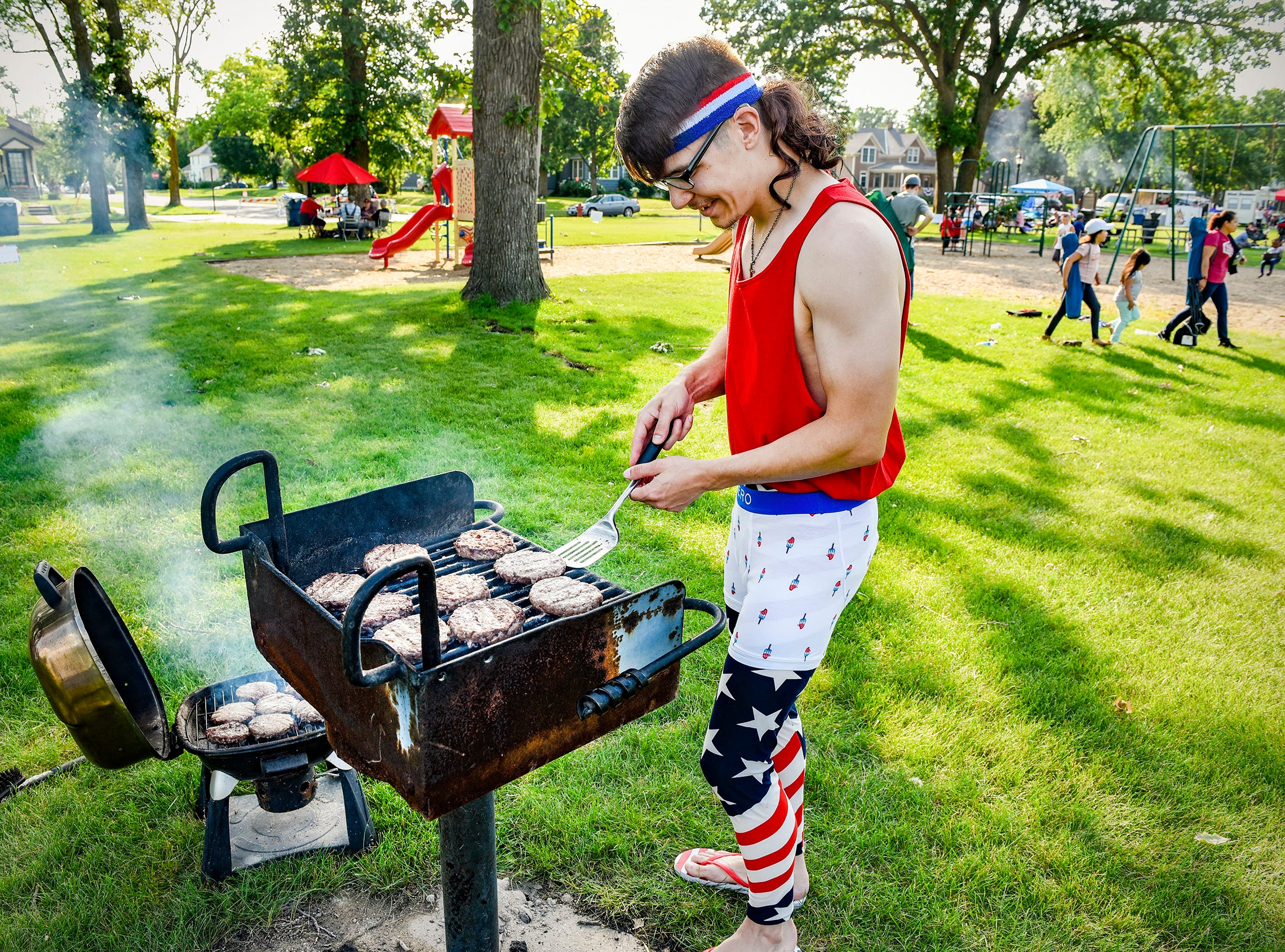 Chuck Schumacher wrangles a pair of grills as he makes hamburgers for the family In Hester Park before the fireworks Wednesday, July 4, in St. Cloud.